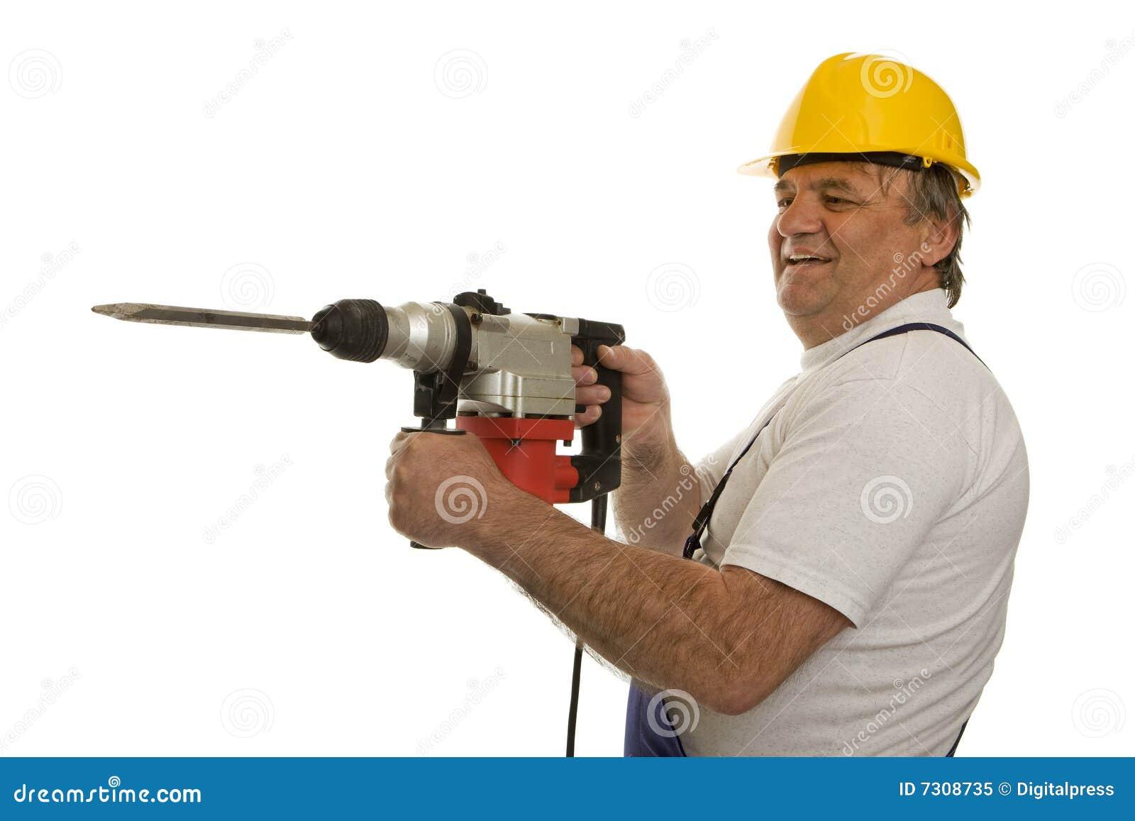 Operaio con la perforatrice ed il casco di sicurezza