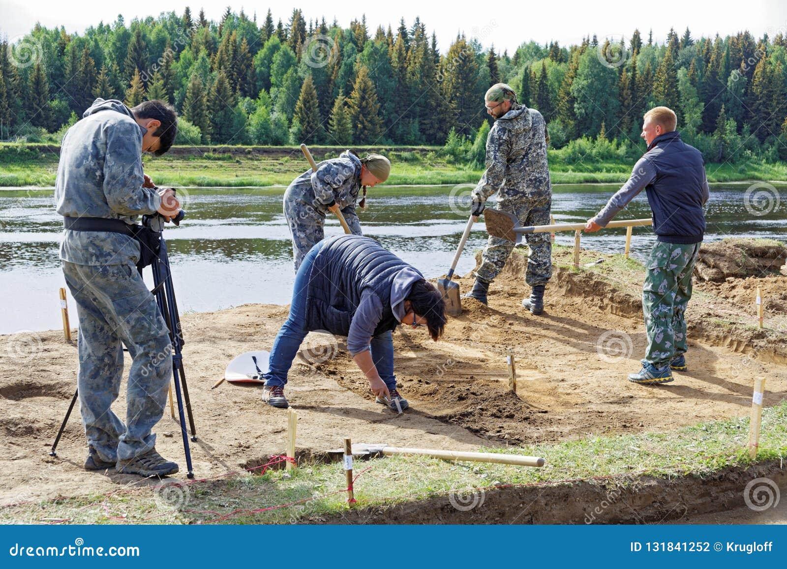Operator bierze wideo grupa ludzi pracuje przy archeologicznymi ekskawacjami na brzeg rzekim