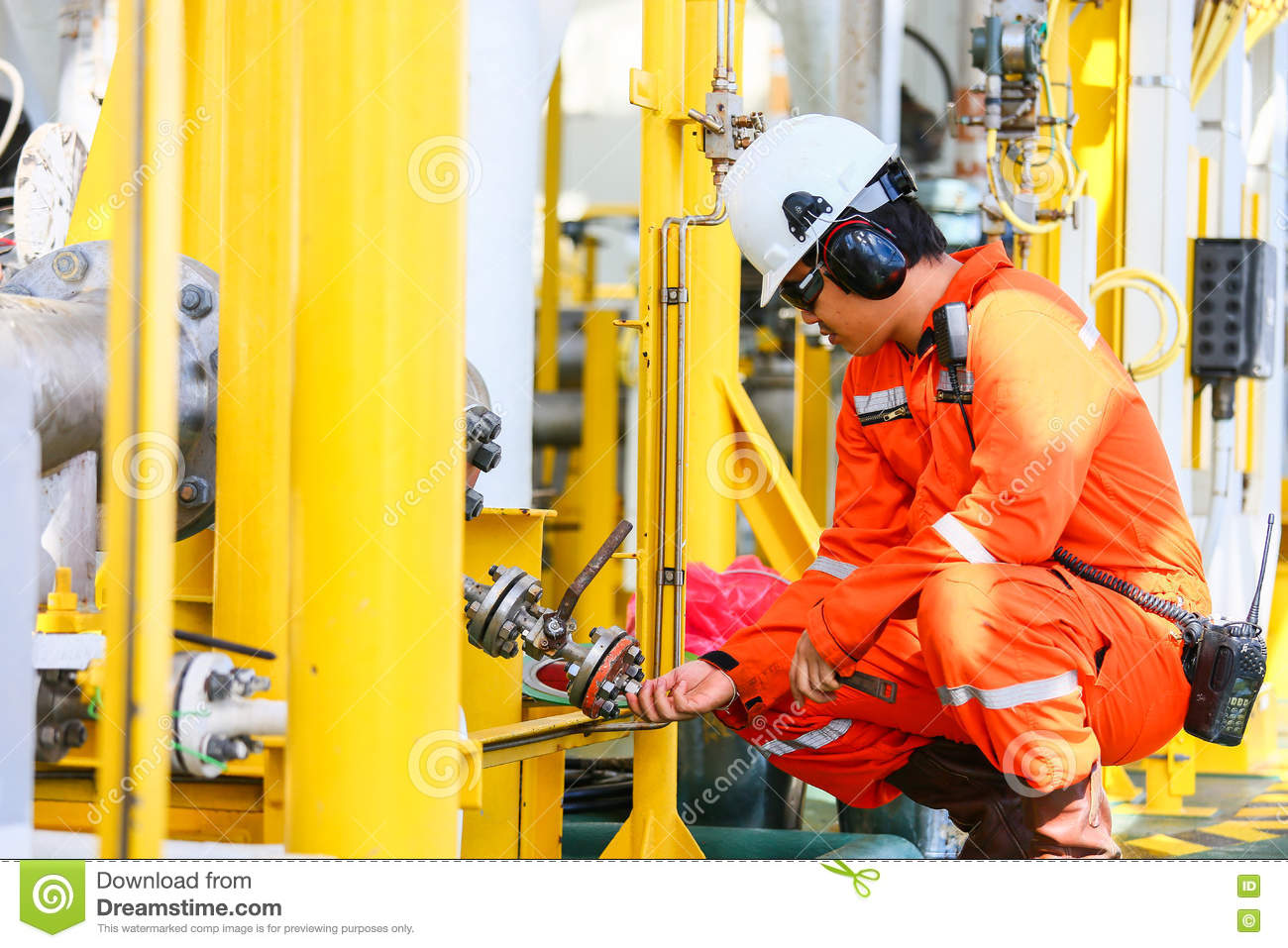 Operator recording operation of oil and gas process at oil and rig plant, offshore oil and gas industry, offshore oil and rig