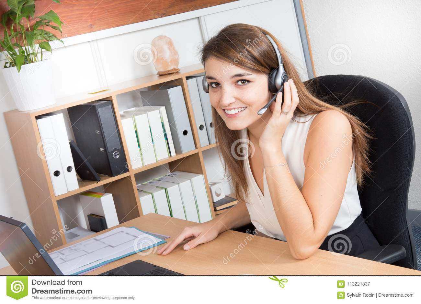 Operatore attraente felice di call-center della giovane donna o cuffia avricolare d uso della ragazza del receptionist
