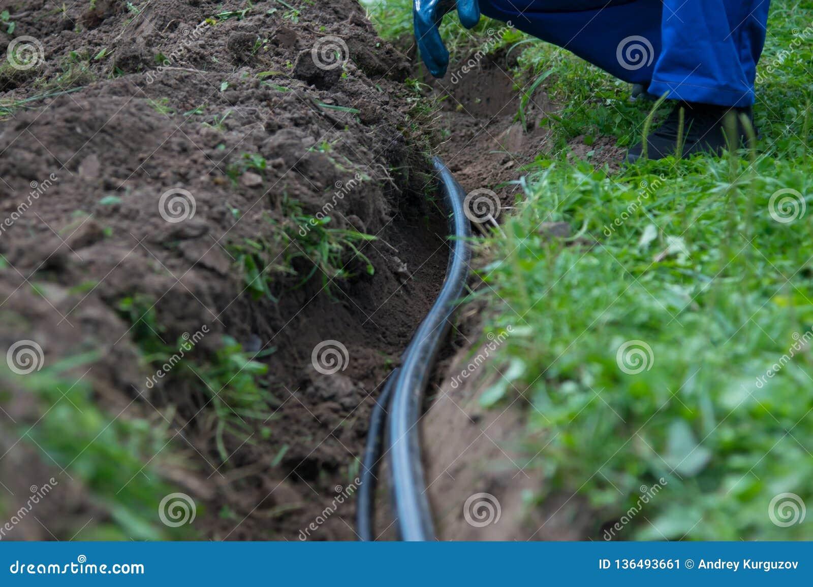 Opgegraven aardegeul voor aanleggen van pijpleidingen van mededeling en elektro bedrading onder de grond om water aan woon te ver