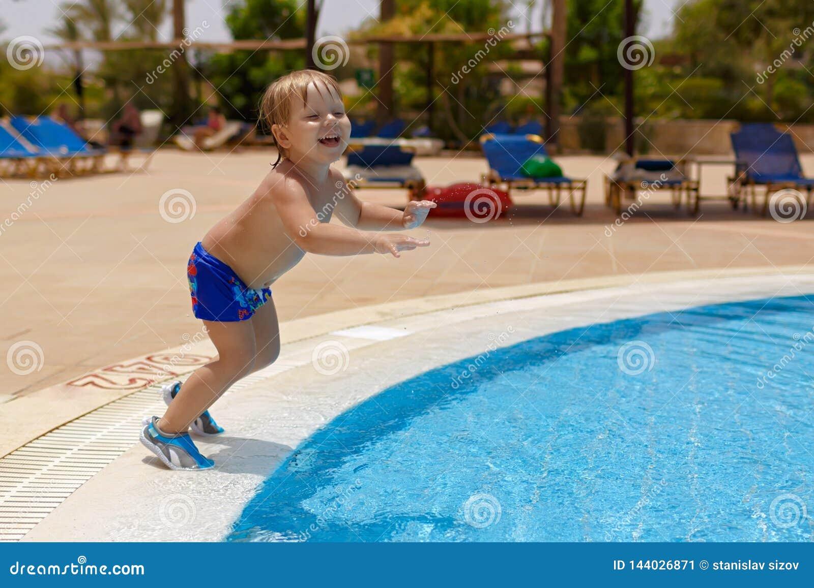 Opgewekte blond-haired kindjongen die in het zwembad gaan springen