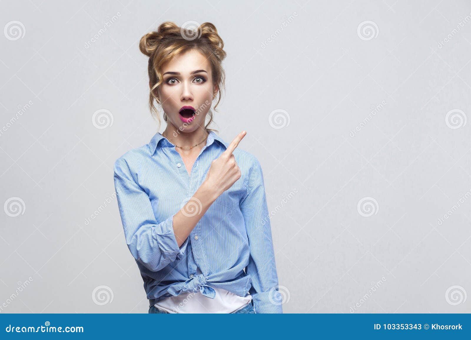 Opgewekte blondevrouw die vinger richten die zijdelings, wenkbrauwen opheffen