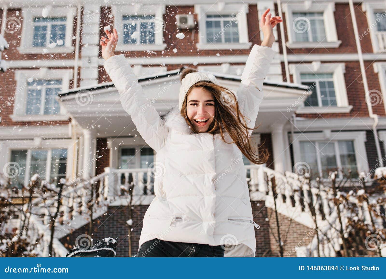Opgewekte brightful emoties van blije vrij jonge vrouw die soround sneeuwval op straat in de wintertijd uitdrukken op huis