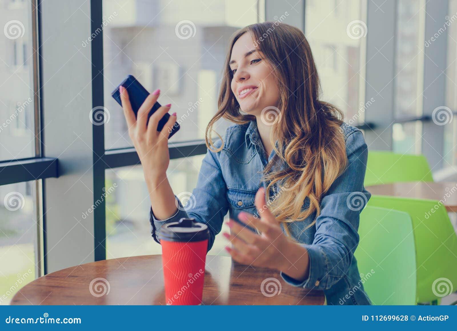 Opgewekte glimlachende gelukkige vrouw die een rust in een koffie hebben, bekijkt zij notific het scherm van haar mobiele telefoo