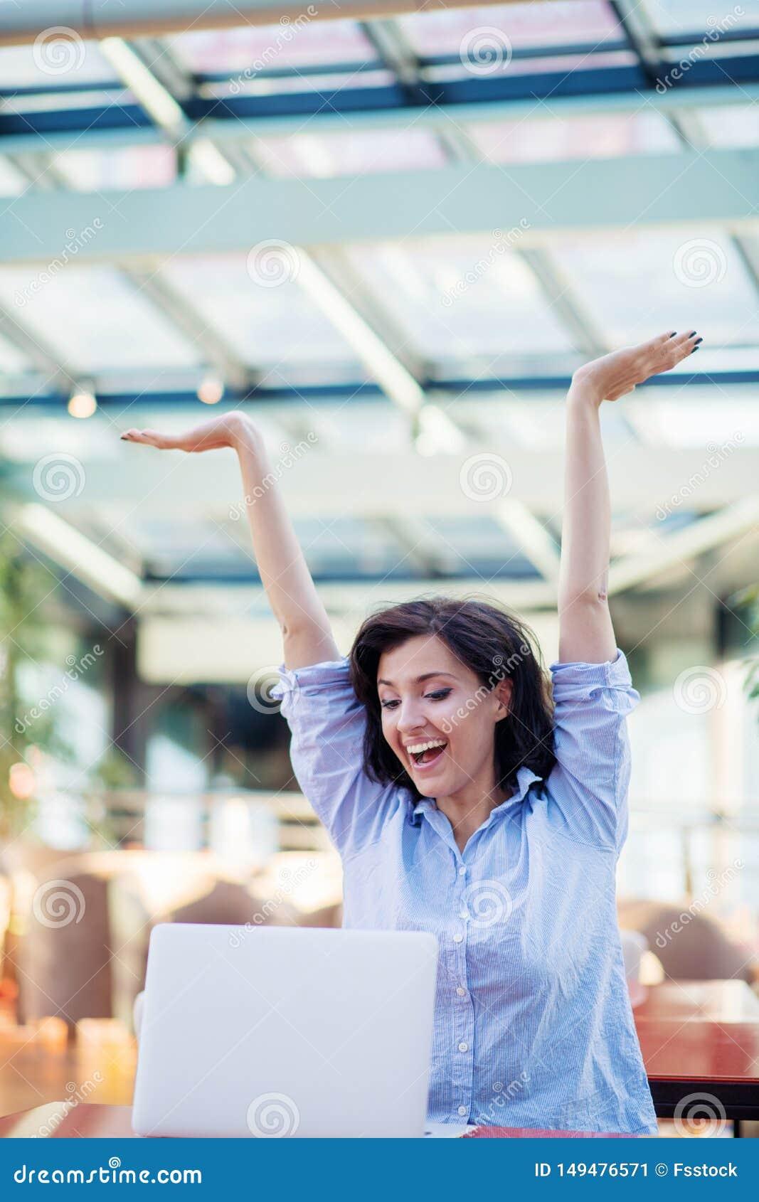 Opgewekte glimlachende vrouw die online winst vieren, die laptop in koffie met behulp van, bekijkend scherm, die met het opheffen