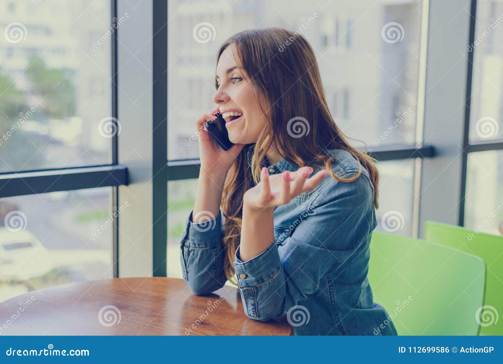 Opgewekte het lachen mooie vrouwenzitting in een koffie, spreekt zij op telefoon en roddelt met haar beste vriend Emotie die ca u