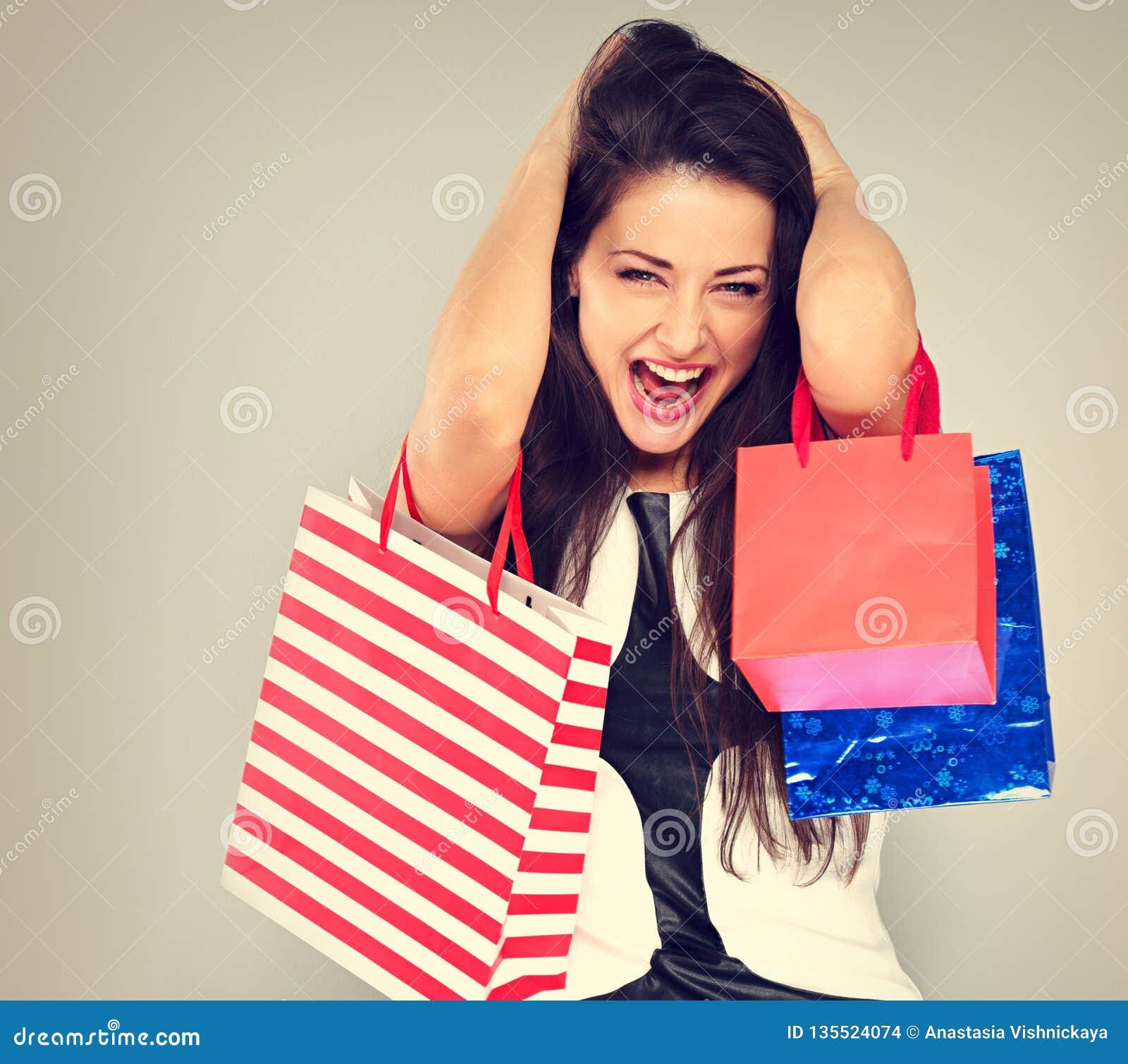 Opgewekte het verrassen schreeuwende vrouw met geopende mond in manier witte kleding met het winkelen zakken De gelukkige verkoop