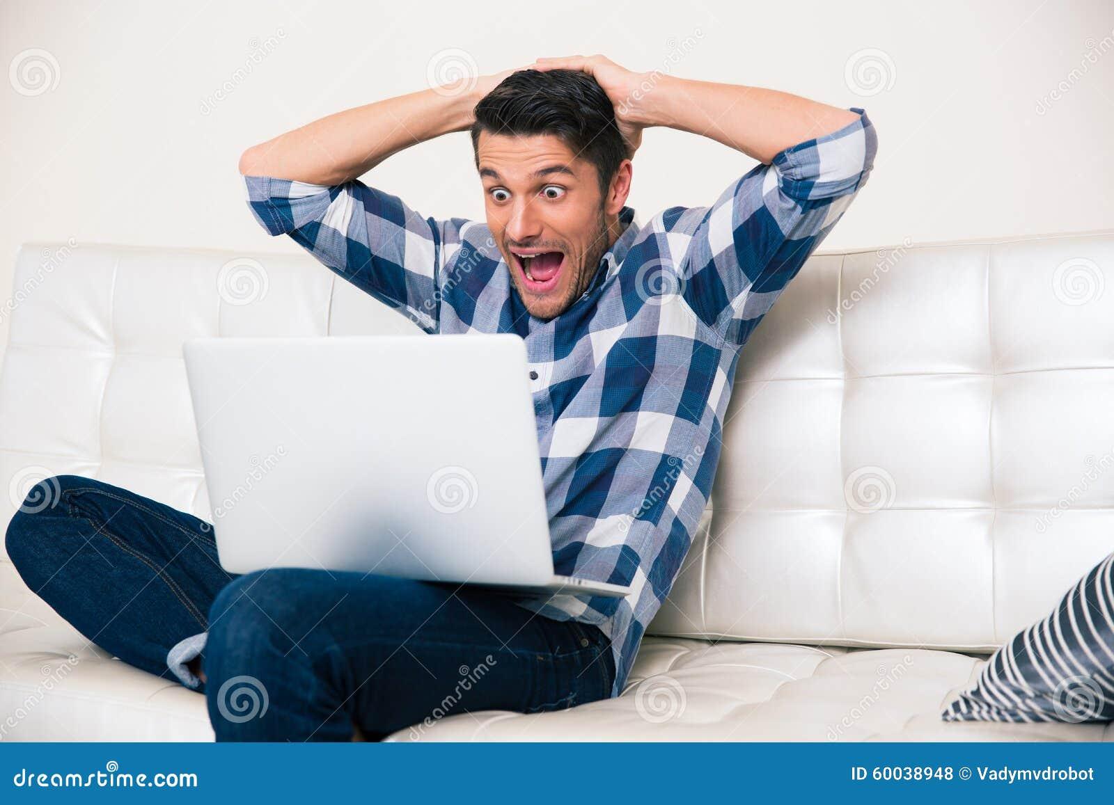Opgewekte mens die spel op laptop kijken