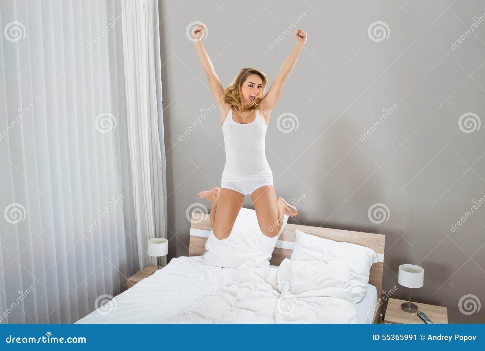 Opgewekte vrouw die op bed springen