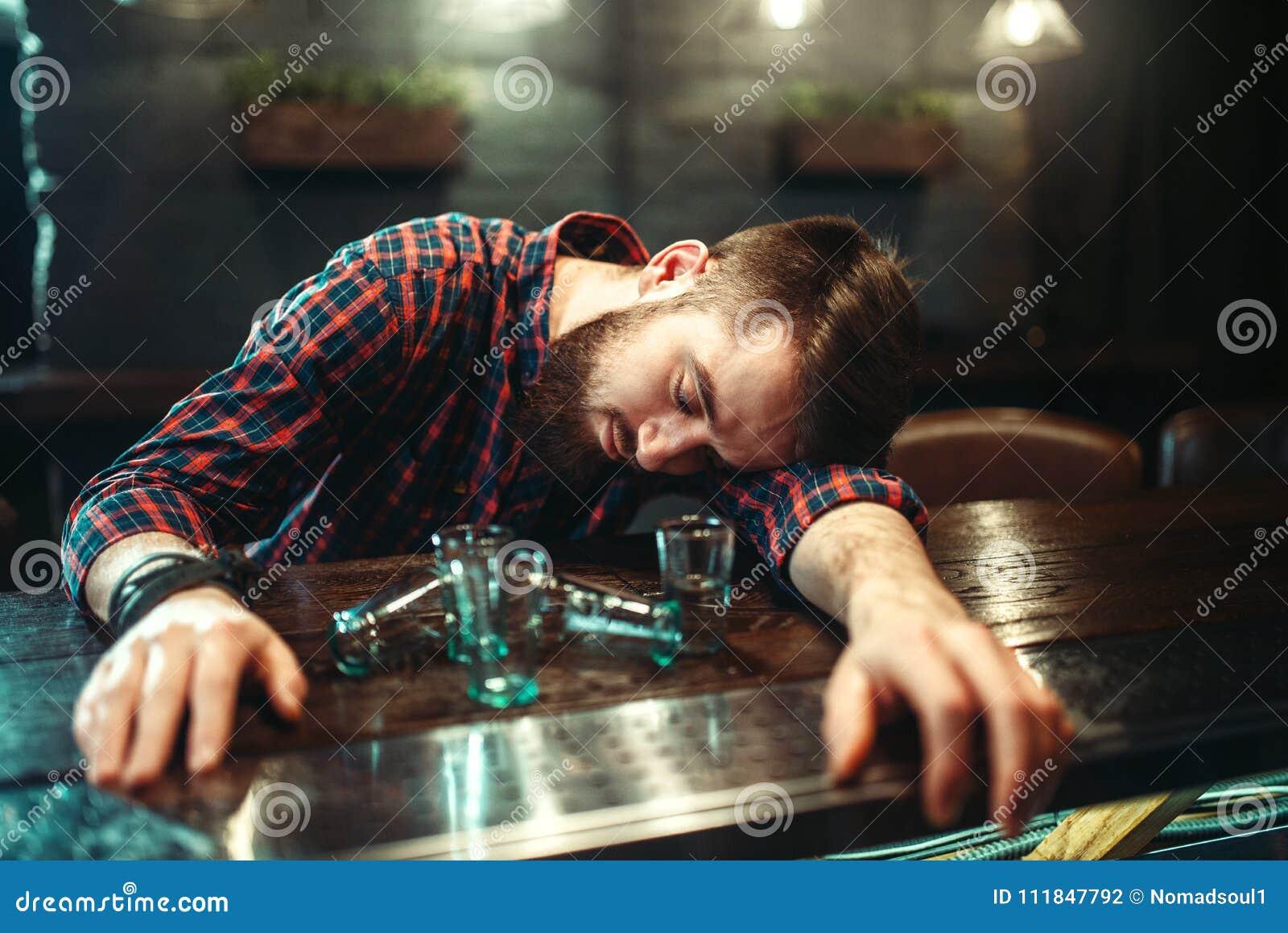 Opiły mężczyzna śpi przy baru kontuarem, alkoholu nałóg