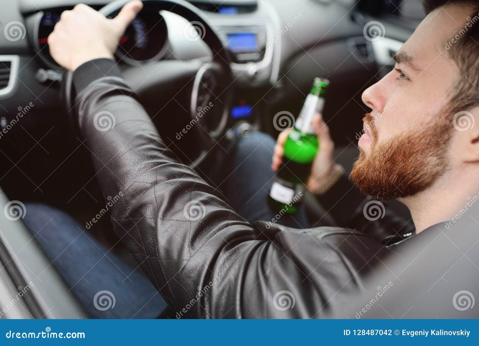 Opiły mężczyzna z butelką piwny jeżdżenie samochód