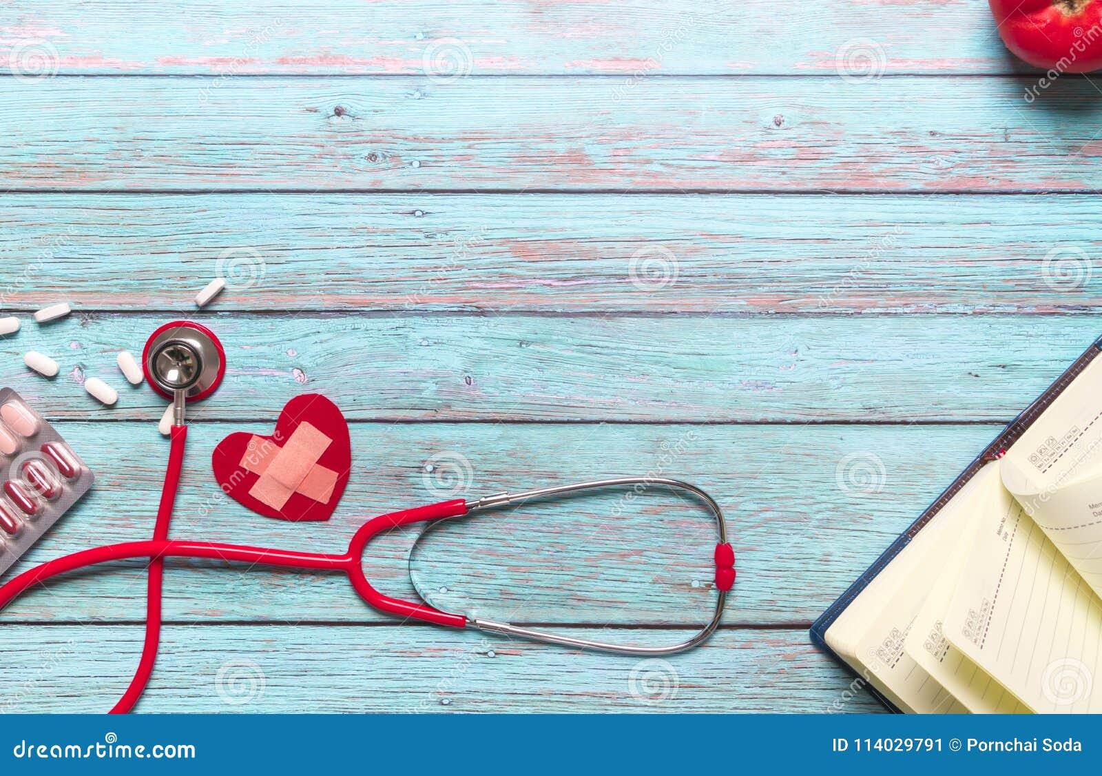 Opieka zdrowotna, medycznego pojęcia czerwony stetoskop i medycyna na błękitnym drewnianym tle