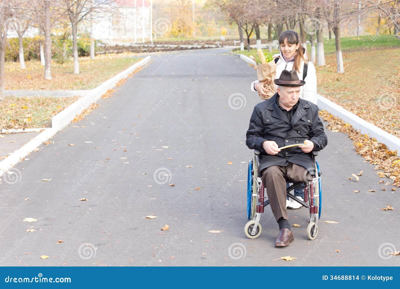 Opiekun pomaga niepełnosprawnego mężczyzna w wózku inwalidzkim