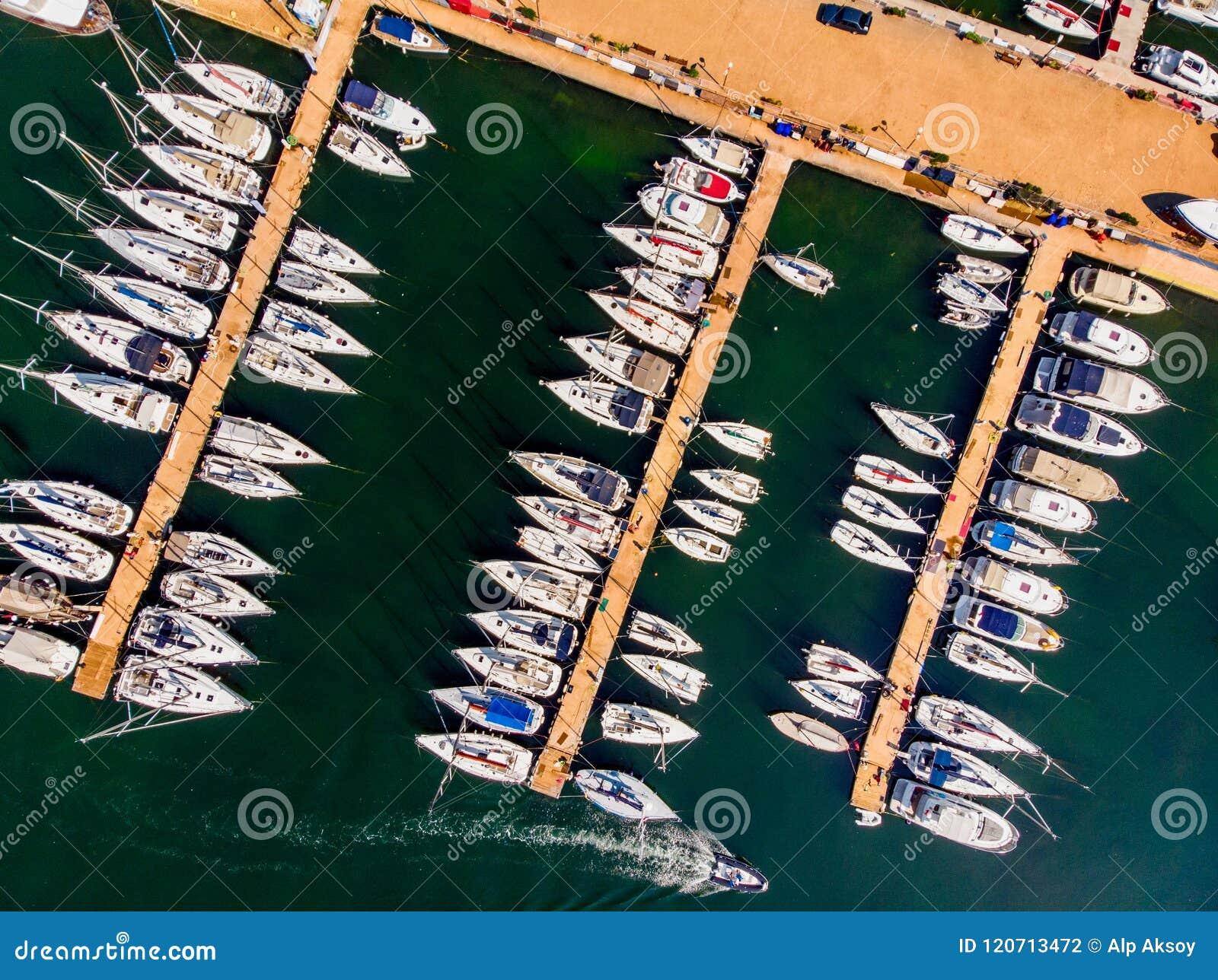 Opinião aérea do zangão do porto com os veleiros e os barcos de motor entrados no cais