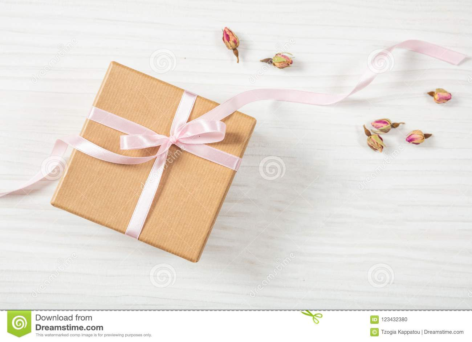 Opinião ascendente e superior do fim da caixa de presente bege do ofício com a fita de seda cor-de-rosa em um fundo de madeira, e
