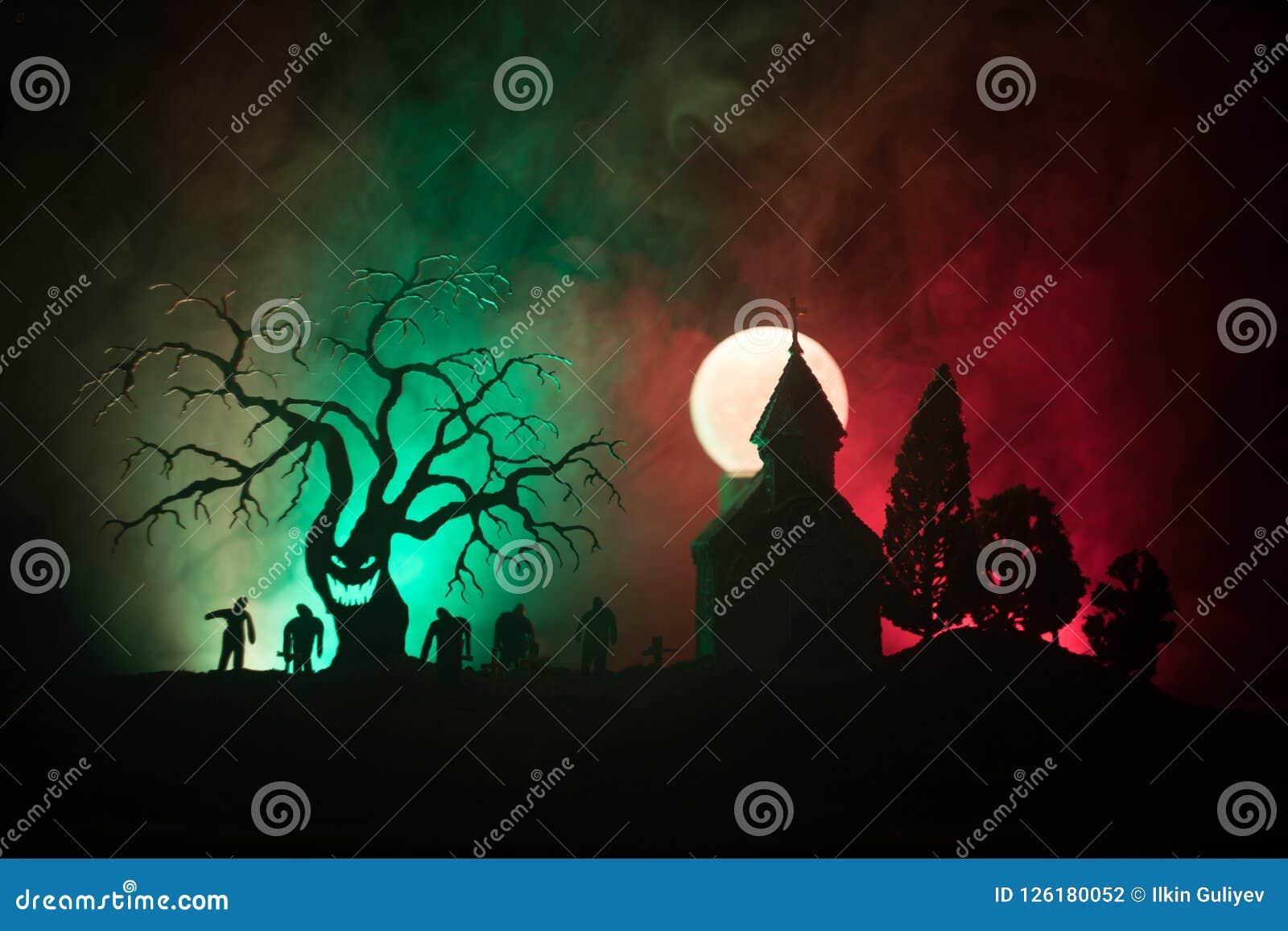 Opinião assustador os zombis na árvore inoperante do cemitério, na lua, na igreja e no céu nebuloso assustador com névoa, conceit