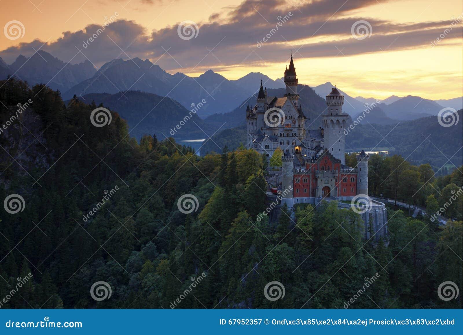 Opinião bonita da noite do castelo de Neuschwanstein do conto de fadas, com cores do outono durante o por do sol, cumes bávaros,