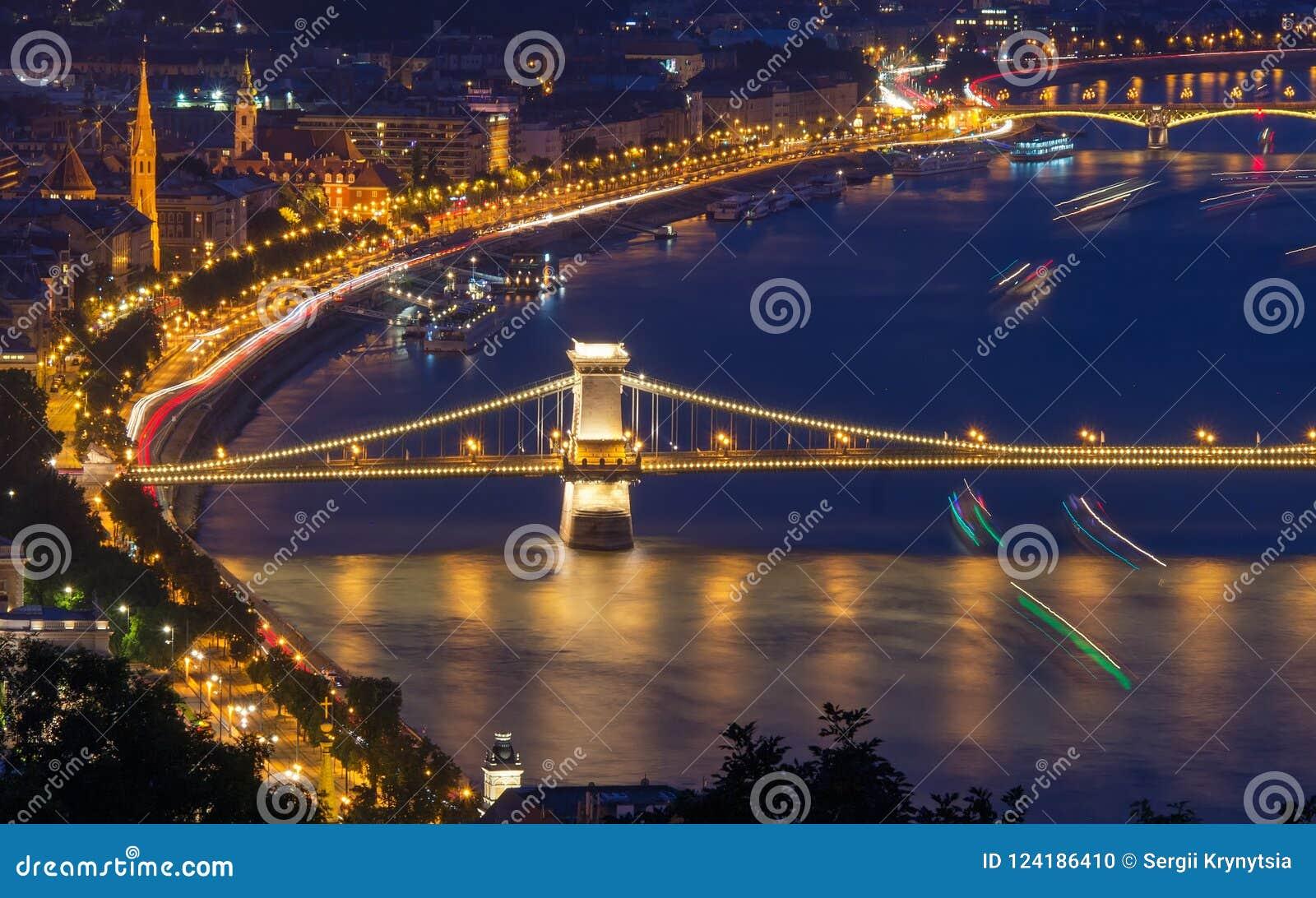 Opinião cênico da noite da ponte Chain e da terraplenagem em Danube River em Budapest, Hungria