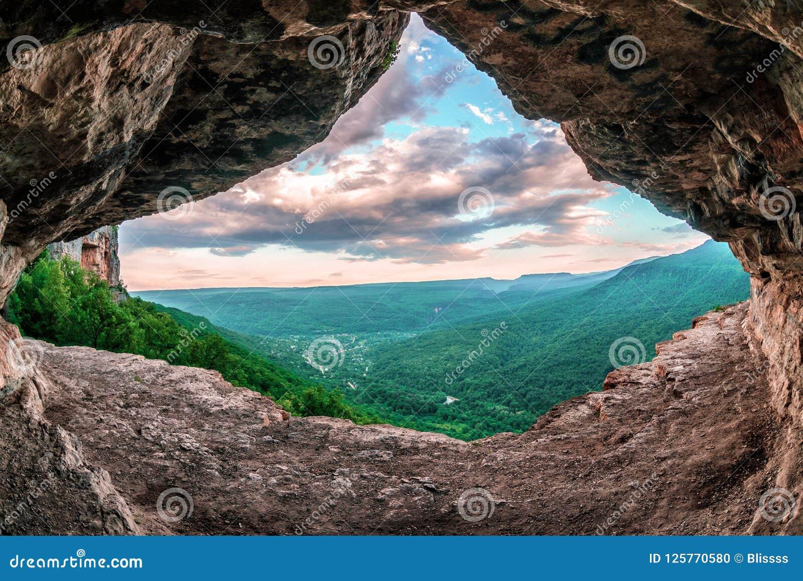 Opinião cênico da paisagem do verão da vila de Mezmay do interior da gruta rochosa estranha em montanhas de Cáucaso, prateleira d