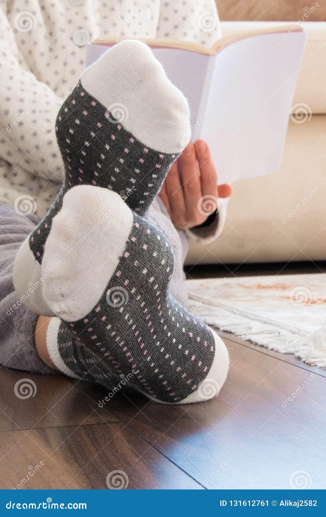 Opinião colhida a mulher com os pijamas que sentam-se no assoalho de madeira em casa com bebida e as cookies quentes, lendo um li
