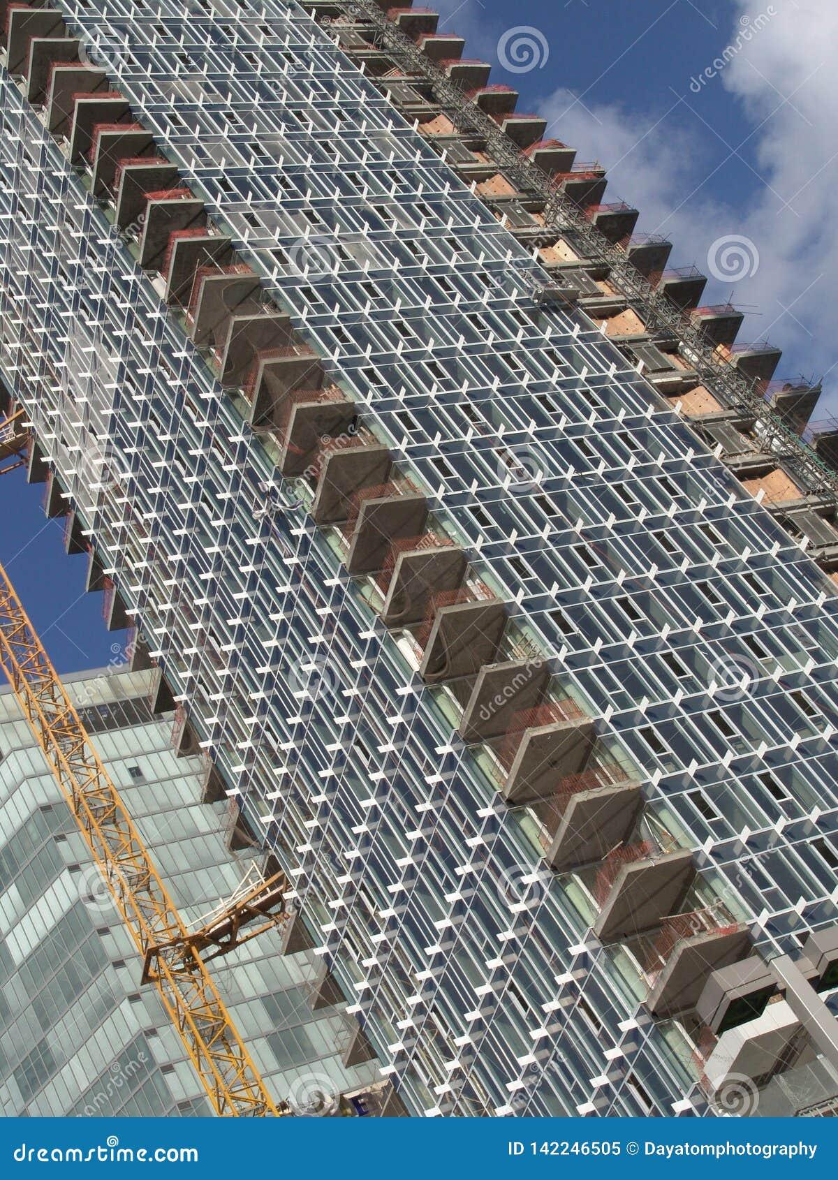 Opinião da esquina da rua de um canteiro de obras de uma construção do arranha-céus