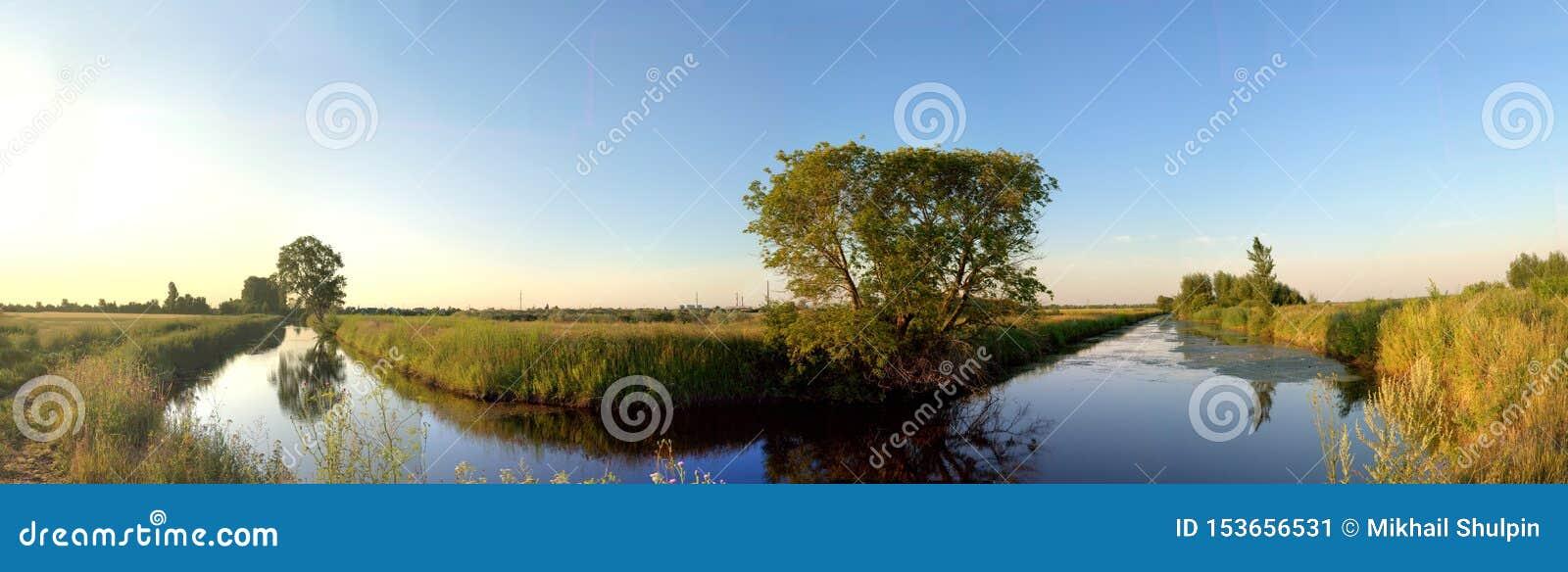 Opinião da manhã do canal e das árvores da irrigação refletidos na água