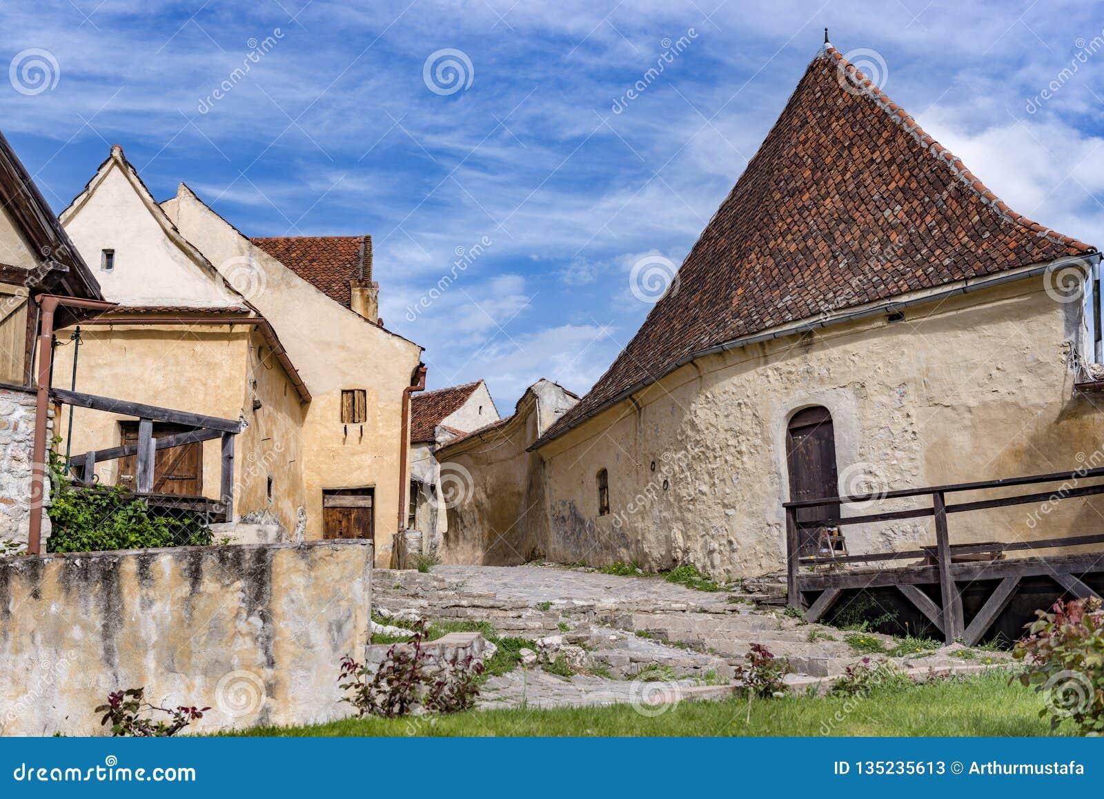 Opinião da mola do countryard interno da citadela de Rasnov, no condado de Brasov (Romênia), com as casas de pedra medievais boni