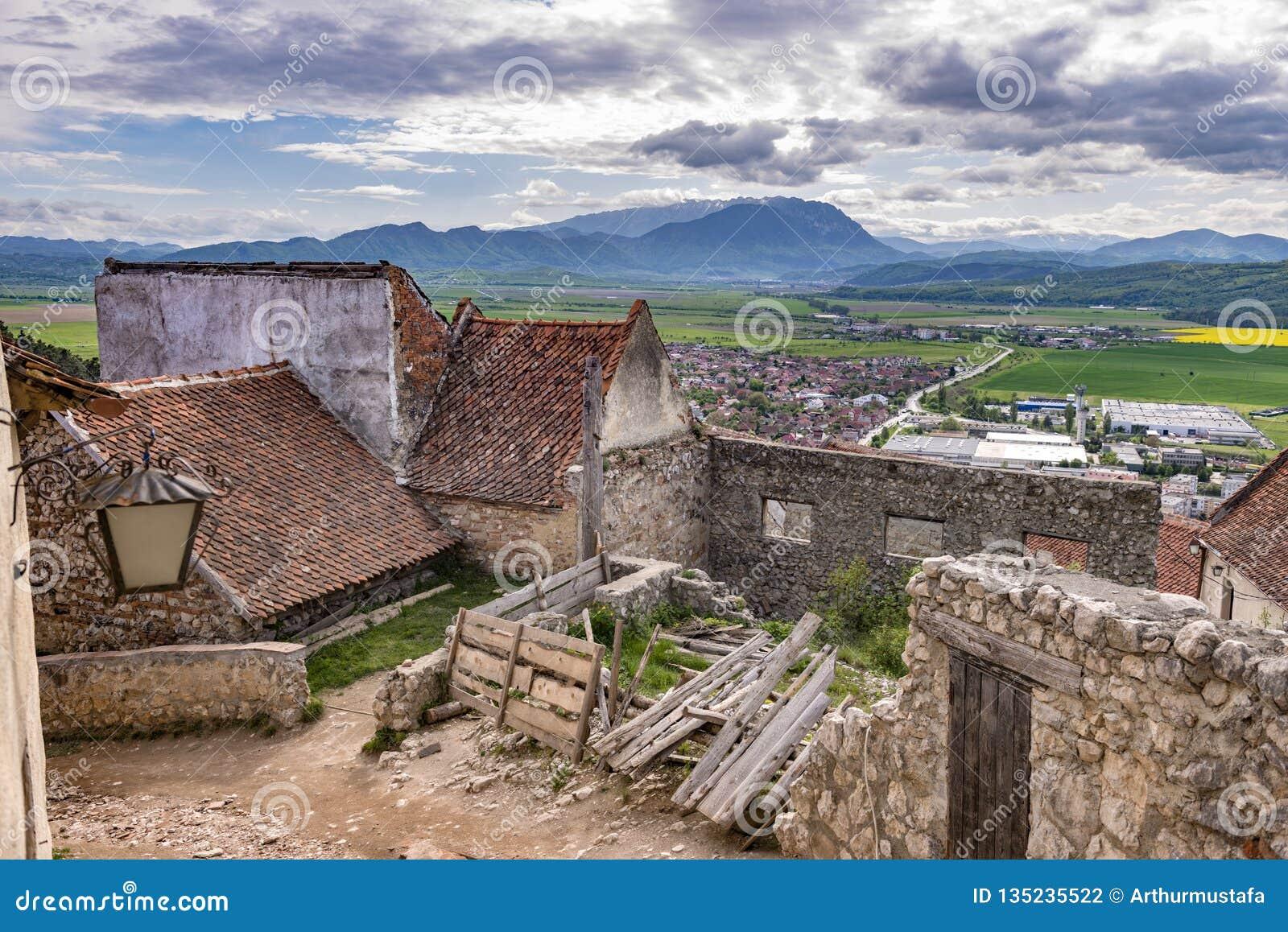 Opinião da mola na citadela de Rasnov, no condado Romênia de Brasov, com as montanhas de Piatra Craiului no fundo