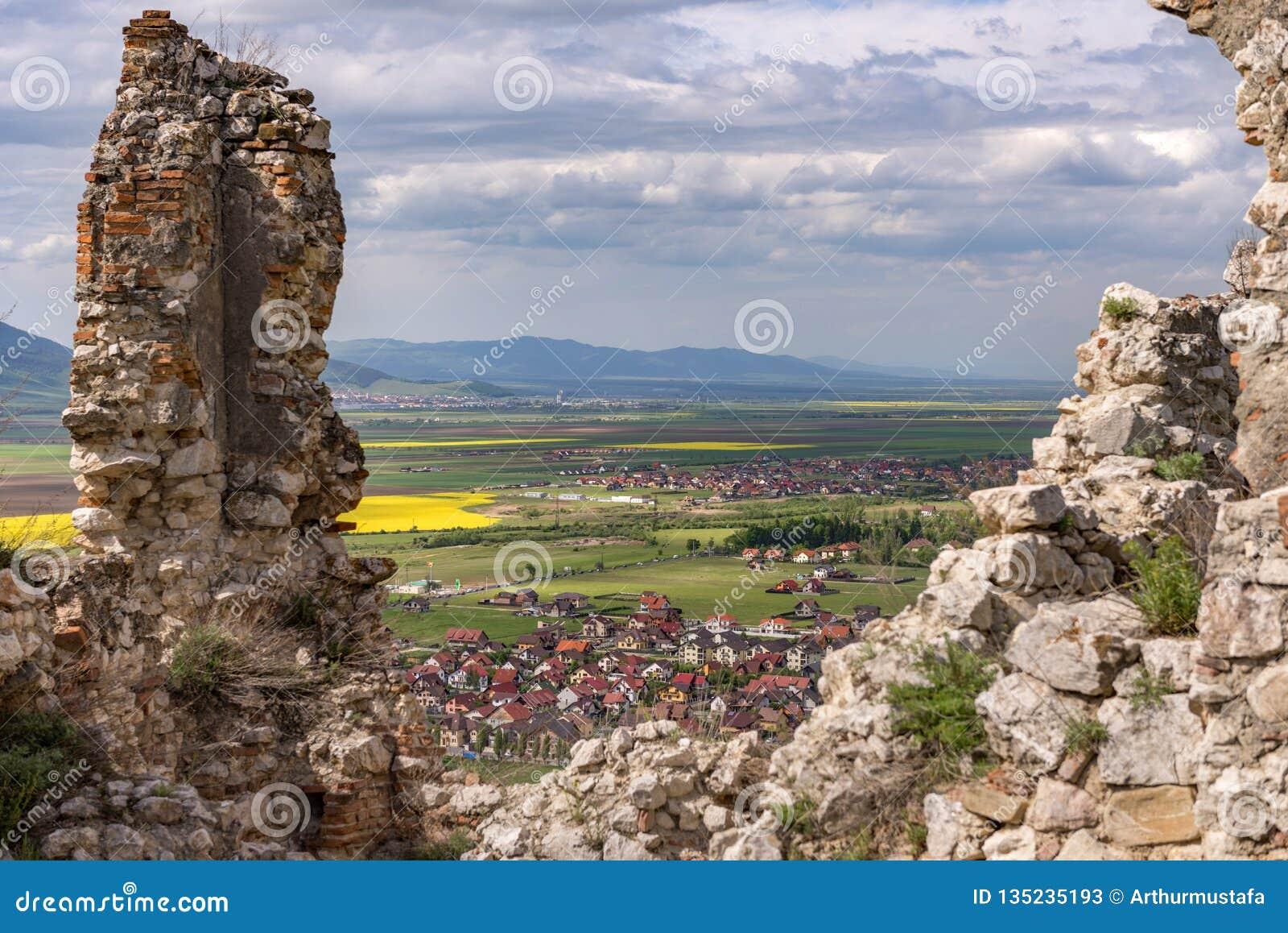 Opinião da mola sobre a cidade de Rasnov através das paredes da citadela de Rasnov, no condado de Brasov (Romênia), com a montanh
