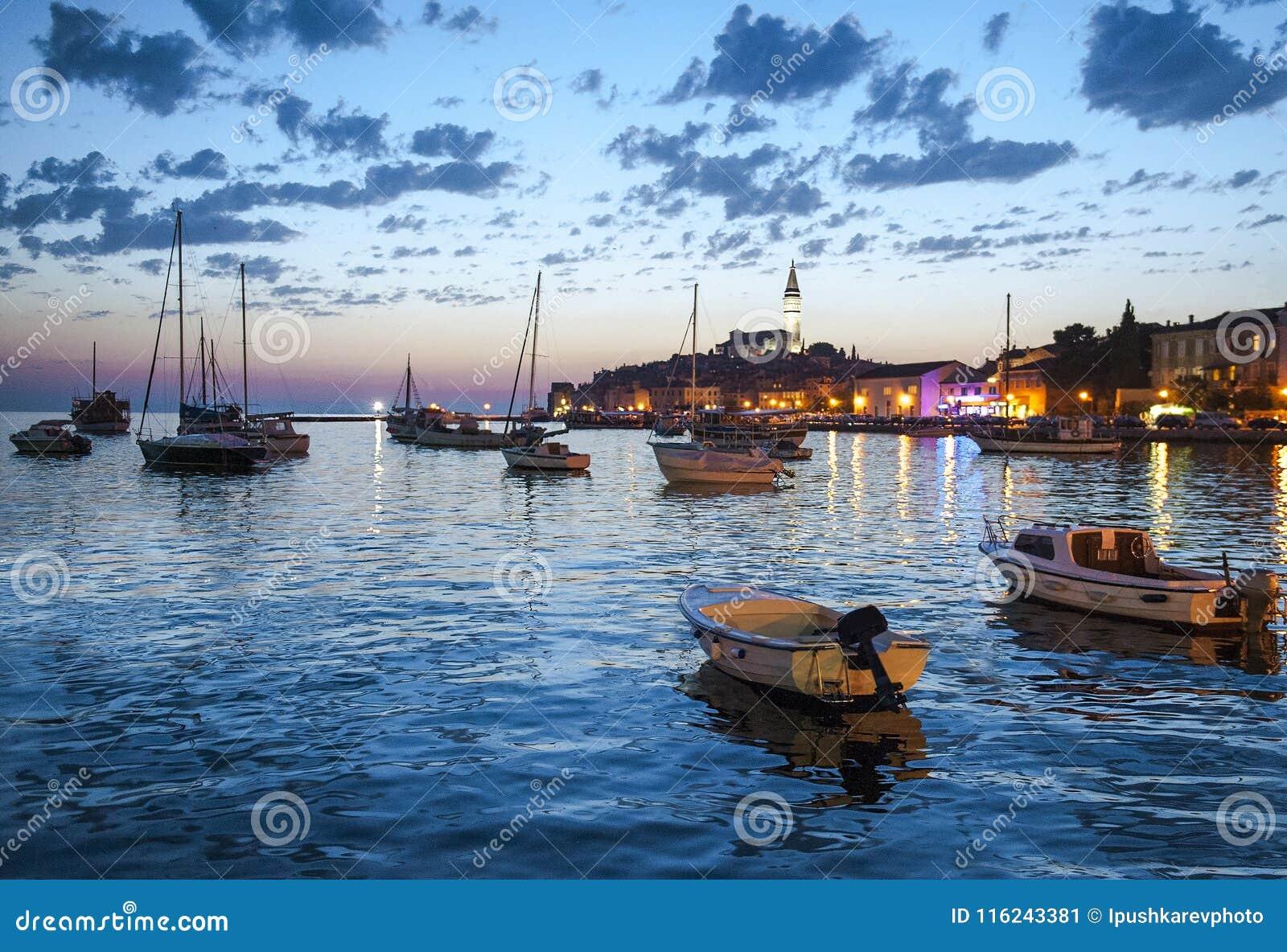 Opinião da noite da cidade bonita Rovinj em Istria, Croácia Noite na cidade croata velha, cena da noite com reflexões da água