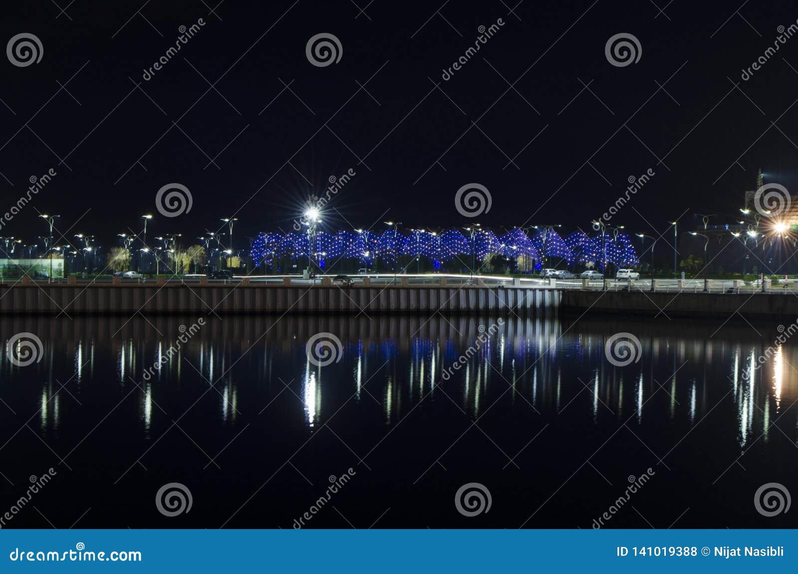 Opinião da noite de Baku com as torres da chama e o bulevar nacional