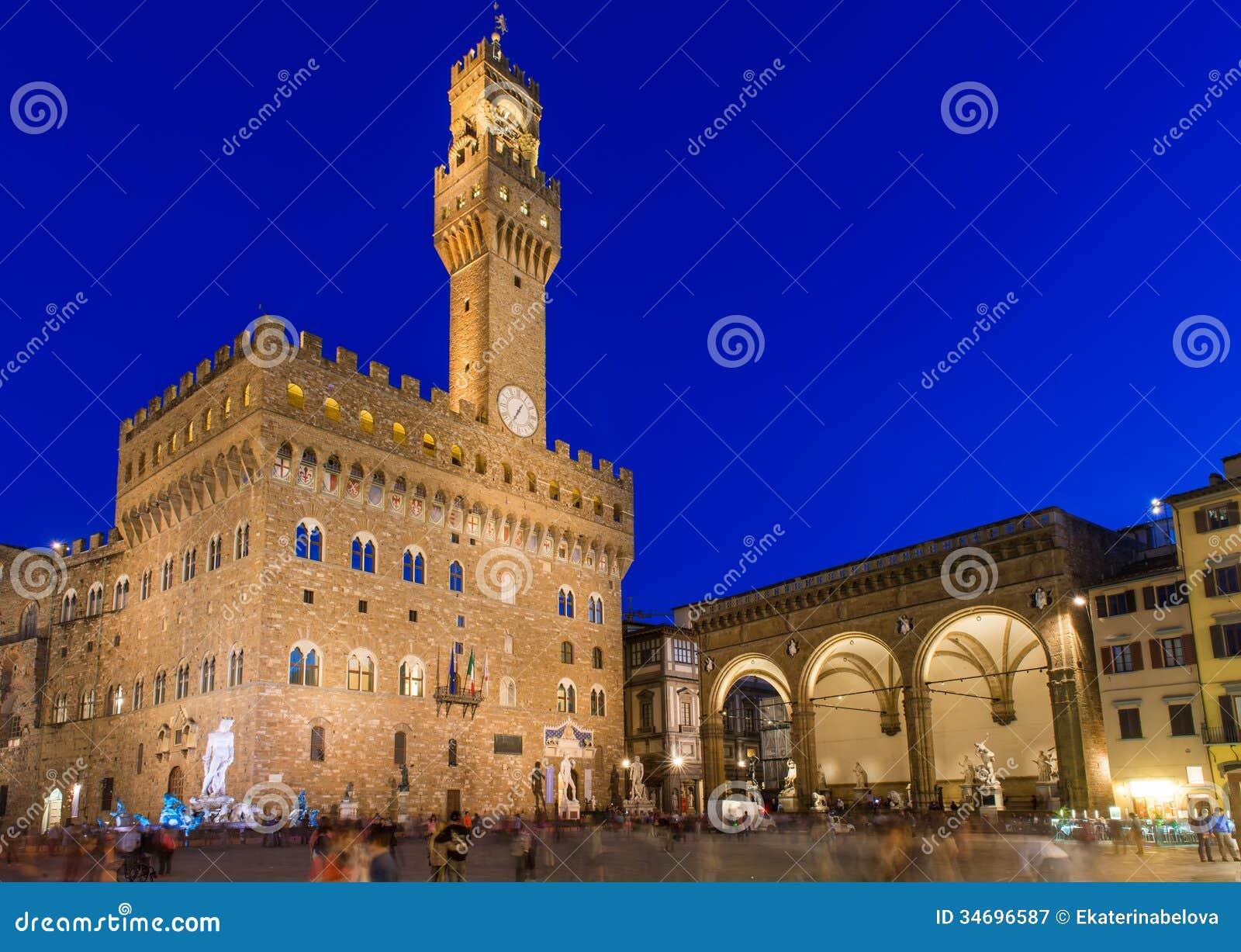 Opinião da noite do della Signoria e Palazzo Vecchio da praça em Florença