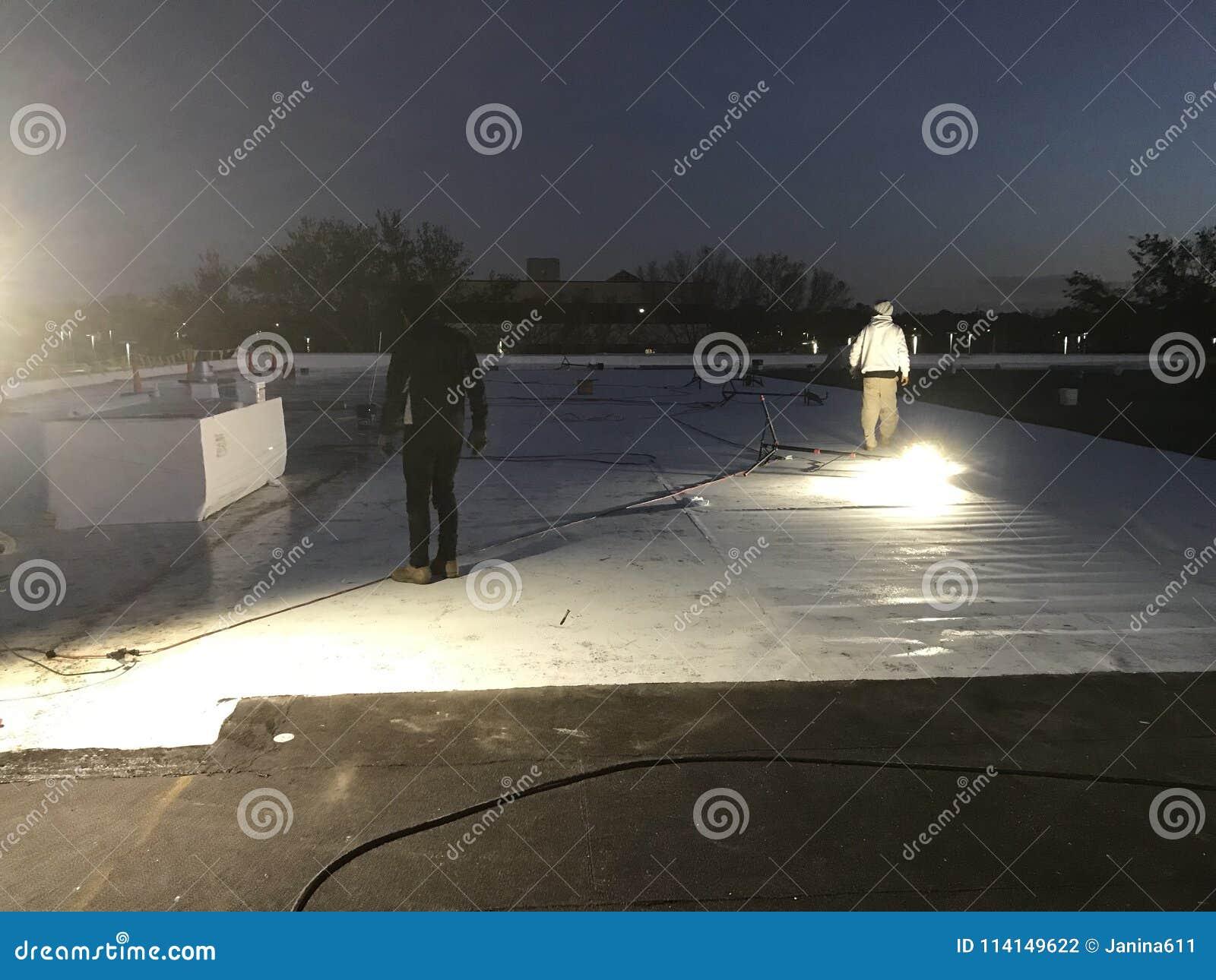 Opinião da noite os Roofers que removem a folha alterada do tampão do telhado liso comercial para a conversão a TPO com as bandei