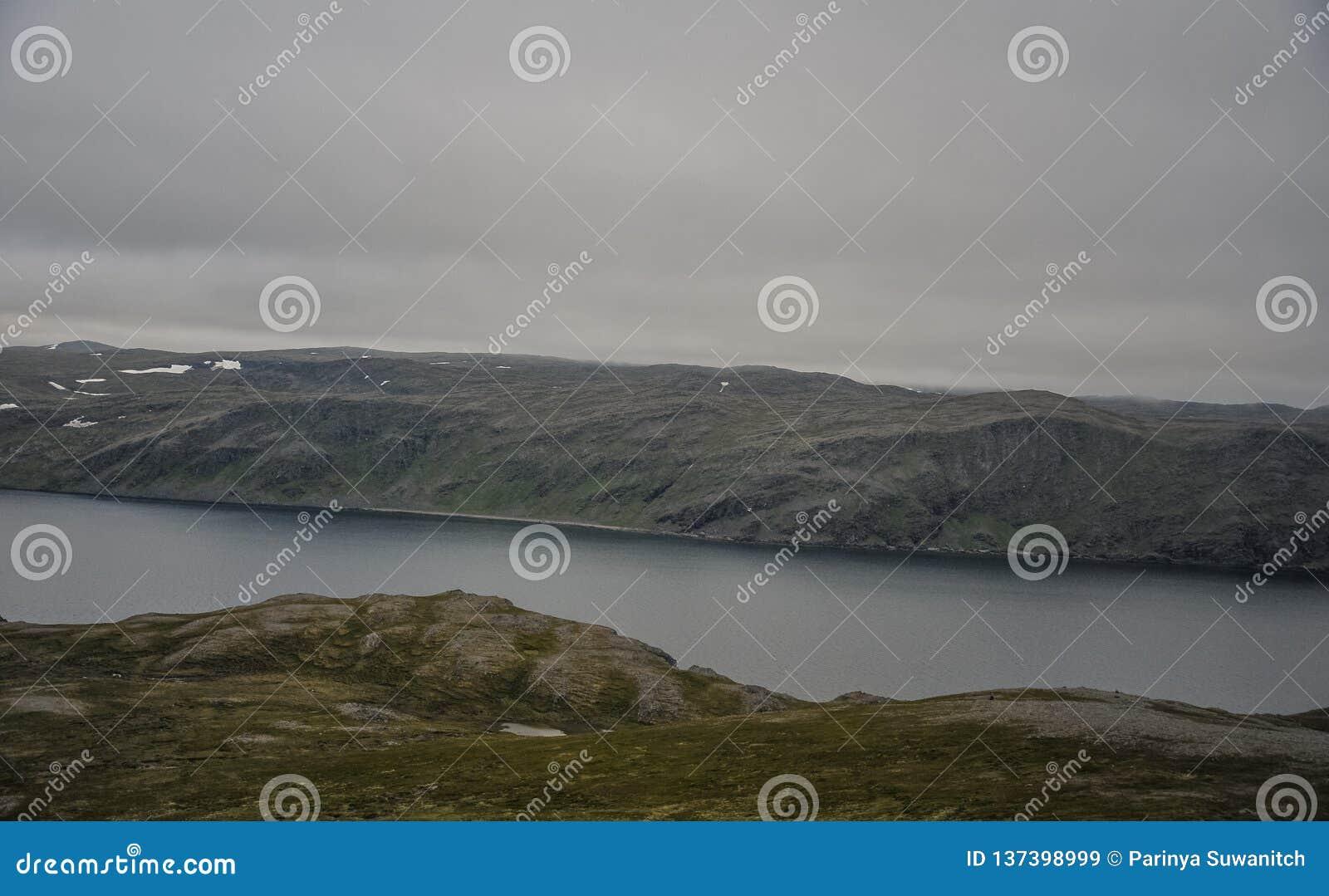 Opinião da paisagem da ilha de Magerøya no condado de Finnmark na maneira ao cabo norte Nordkapp no tempo da meia-noite em Norue