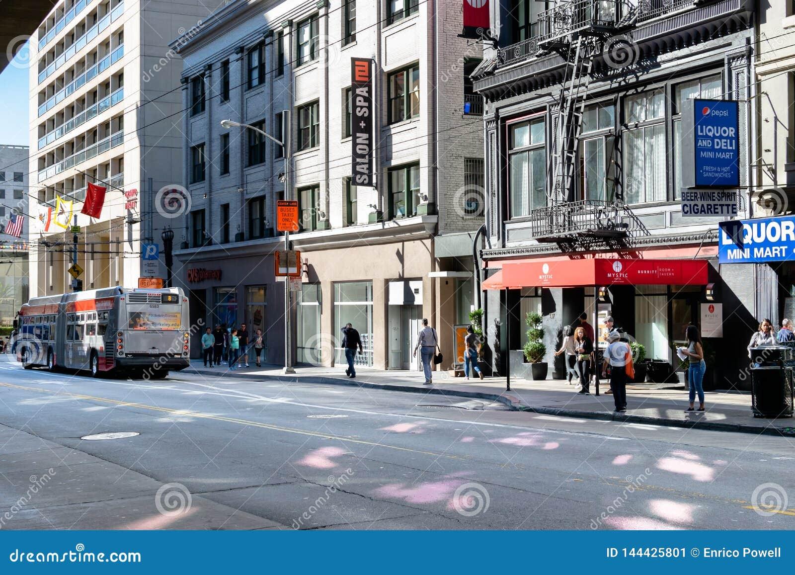 Opinião da rua em San Francisco dos pedestres, das lojas e de um ônibus do MTA