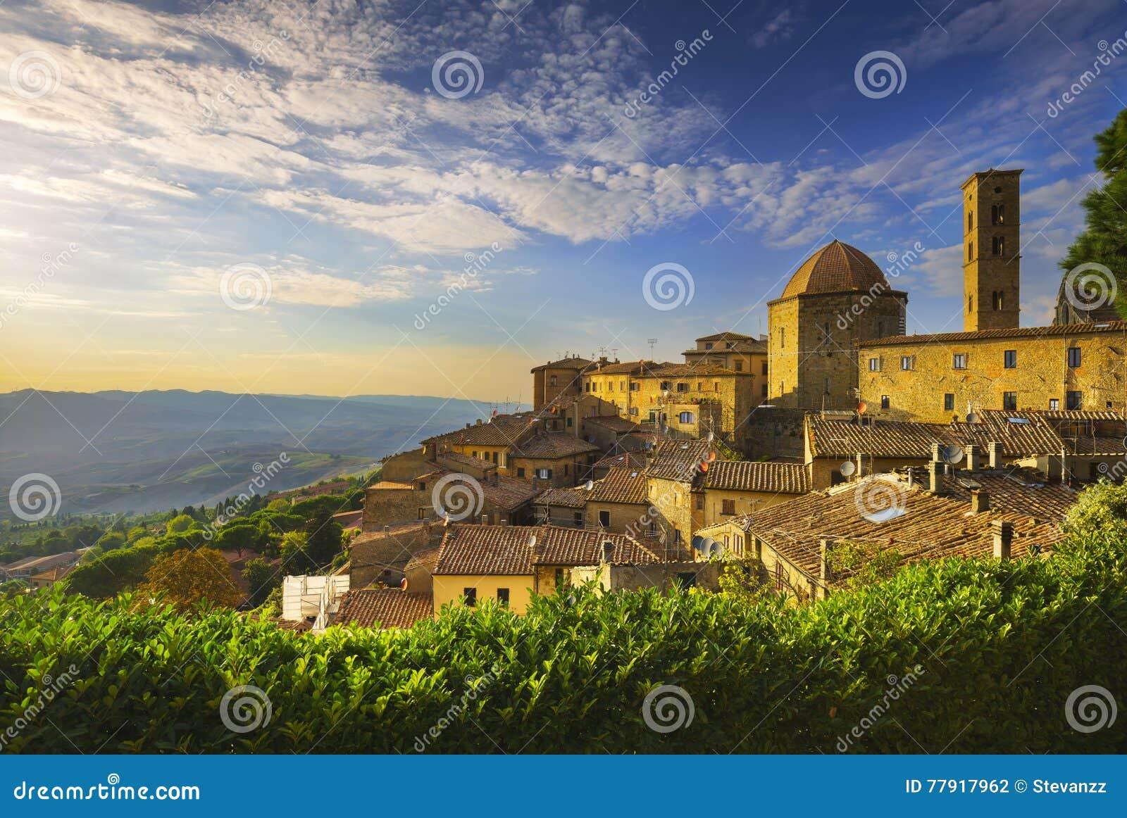 Opinião da skyline da cidade de Toscânia, de Volterra, da igreja e do panorama em sóis