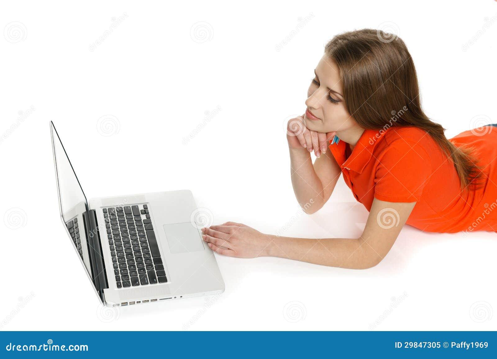 Mulher que encontra-se no assoalho com seu portátil