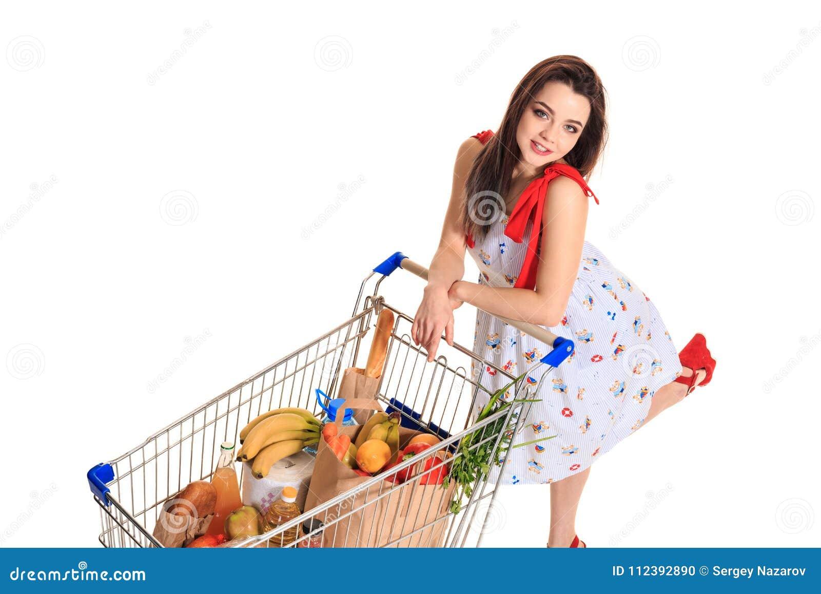 Opinião de ângulo alto a menina que sorri na câmera ao empurrar um carrinho de compras completamente com os mantimentos isolados