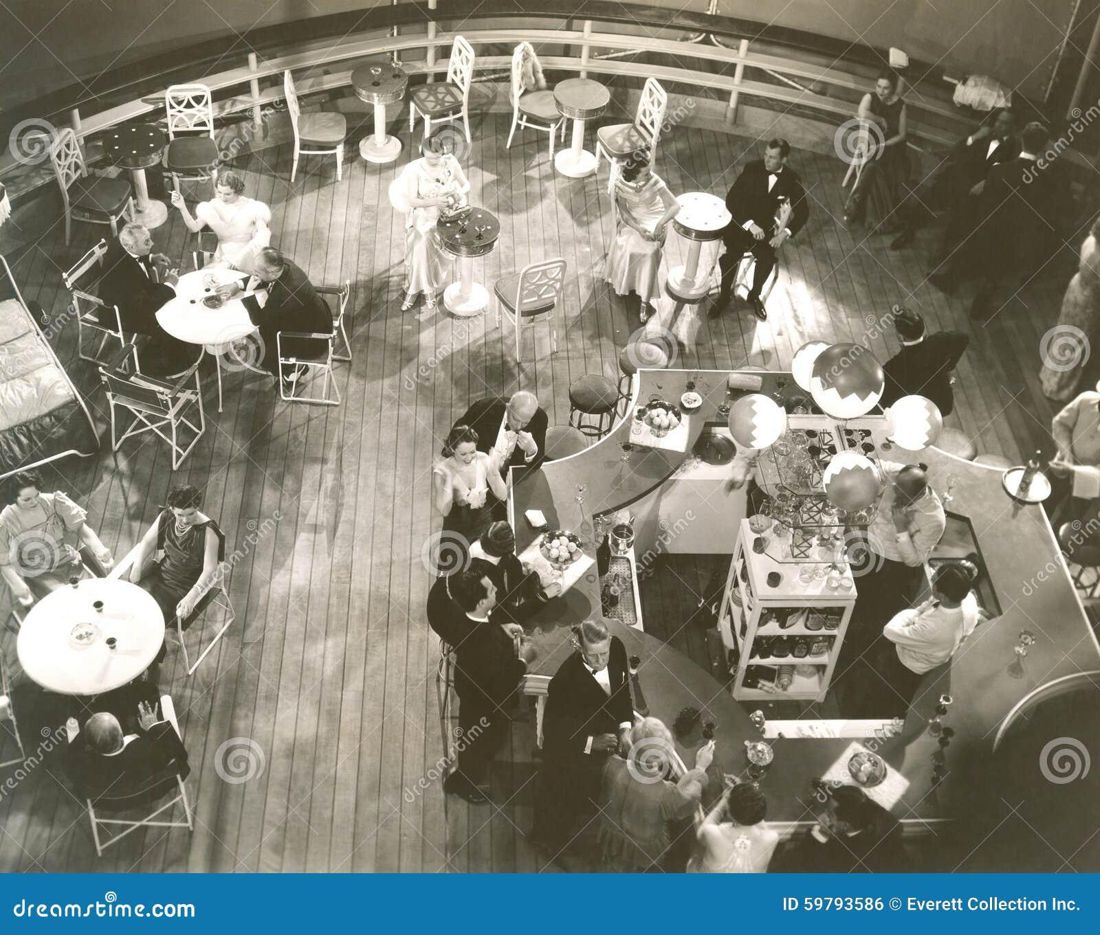 Opinião de ângulo alto os povos na sala de estar de cocktail a bordo do navio