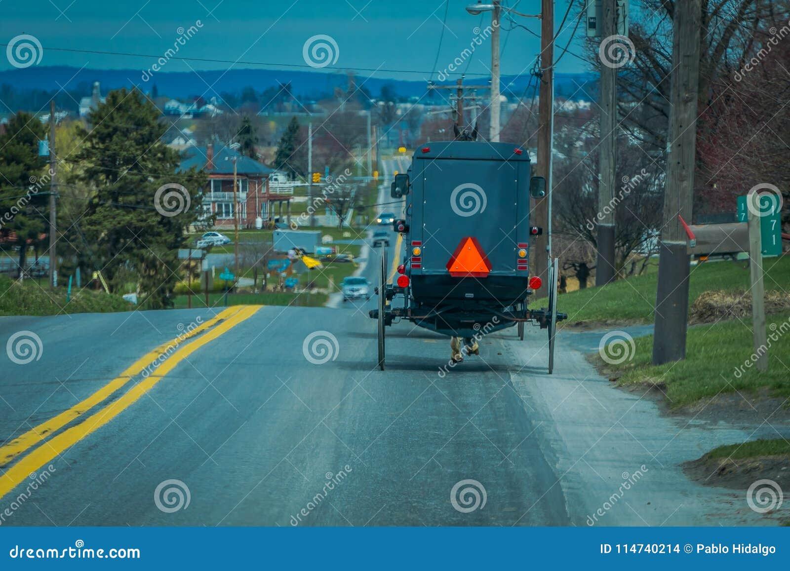 Opinião de Bavck do carrinho de Amish que viaja acima de uma estrada no Condado de Lancaster rural