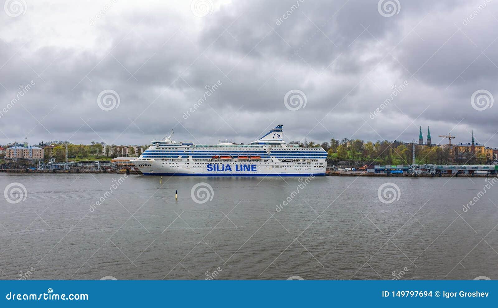 Opinião de dia chuvoso da terraplenagem sul do porto em Helsínquia, Finlandia com a balsa do cruzeiro do carga-passageiro de Silj