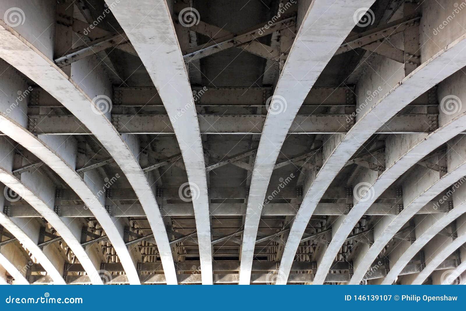 A opinião de perspectiva de vigas de aço arqueadas curvadas sob uma ponte velha da estrada com rebites e suportes pintou cinzento