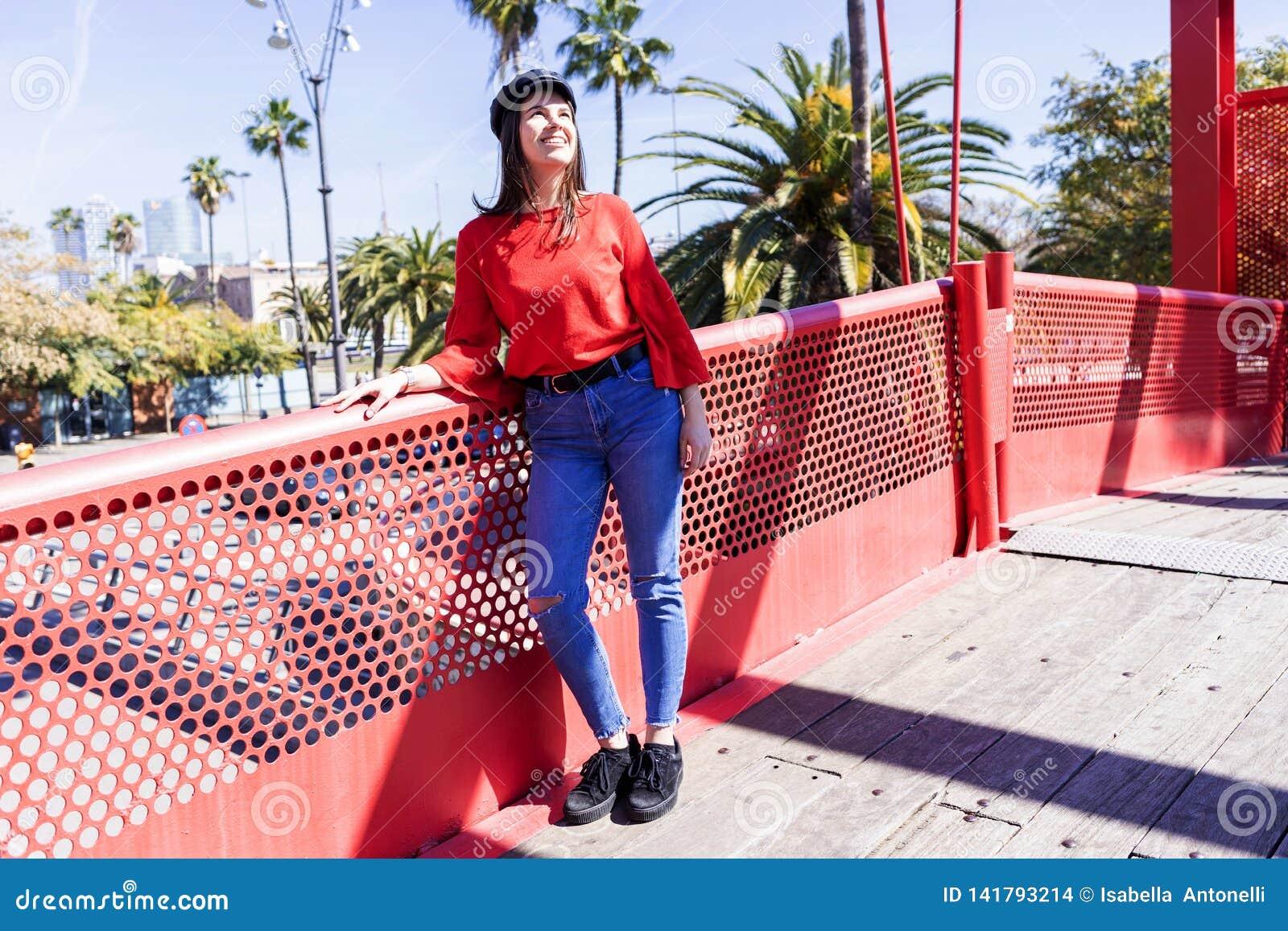 Opinião dianteira uma jovem mulher bonita que veste a roupa urbana que inclina-se em uma cerca metálica da ponte ao olhar afastad
