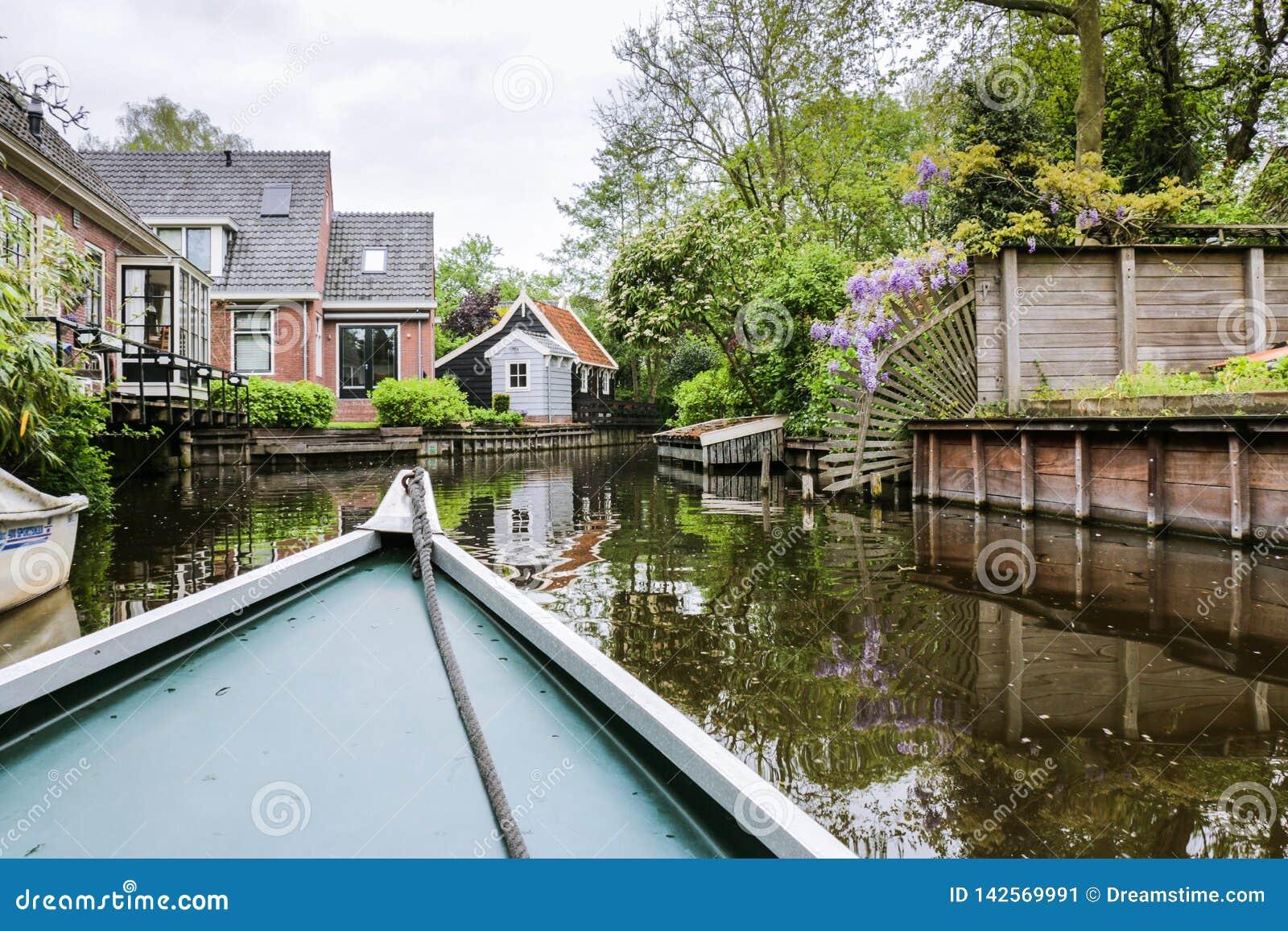 Opinião do barco da cidade rural do canal na Holanda norte