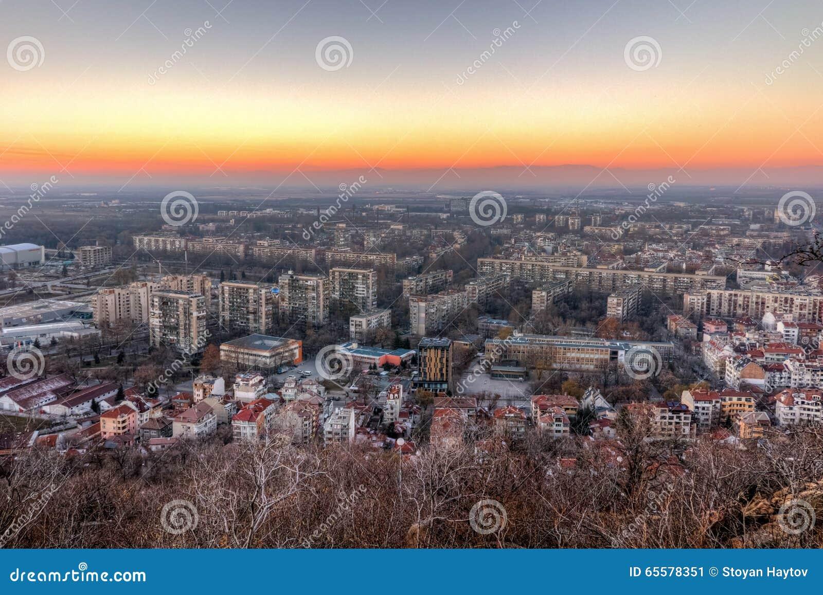 Opinião do por do sol da cidade de Plovdiv do monte do tepe de Dzhendem, Bulgária