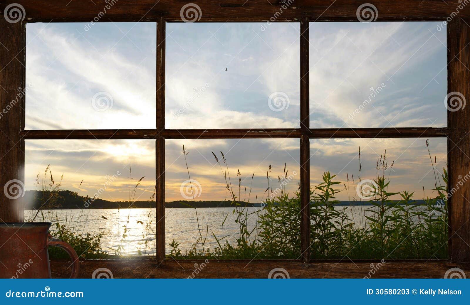 Opinião do por do sol do lago para fora a janela da casa de campo.
