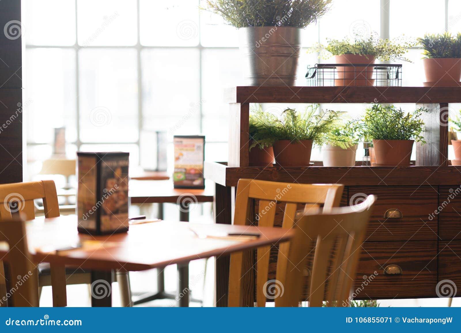 Opinião do restaurante com luz solar e plantas no potenciômetro na decoração
