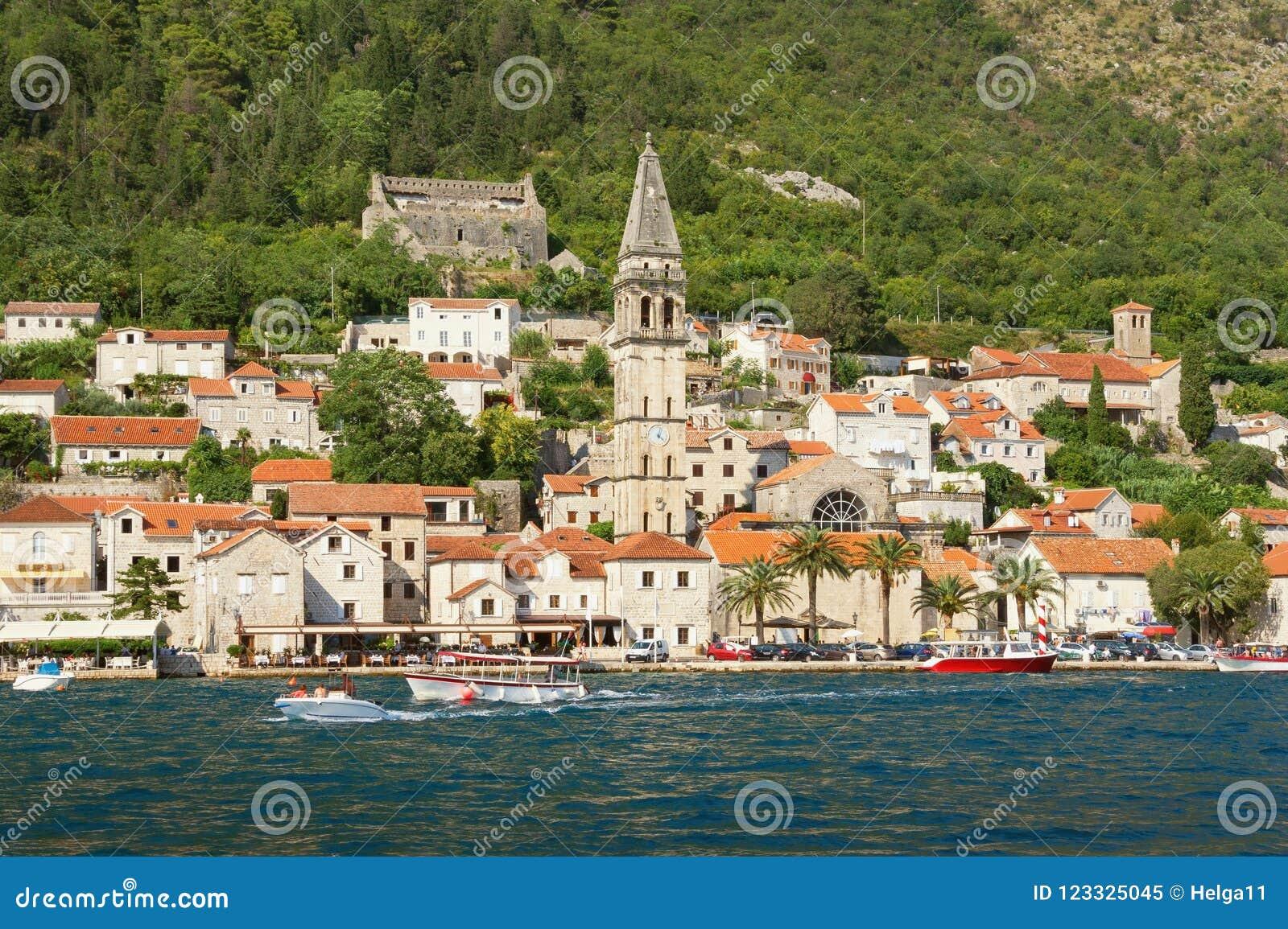 Opinião do verão da cidade antiga de Perast com a torre de sino da igreja de São Nicolau Louro de Kotor, Montenegro