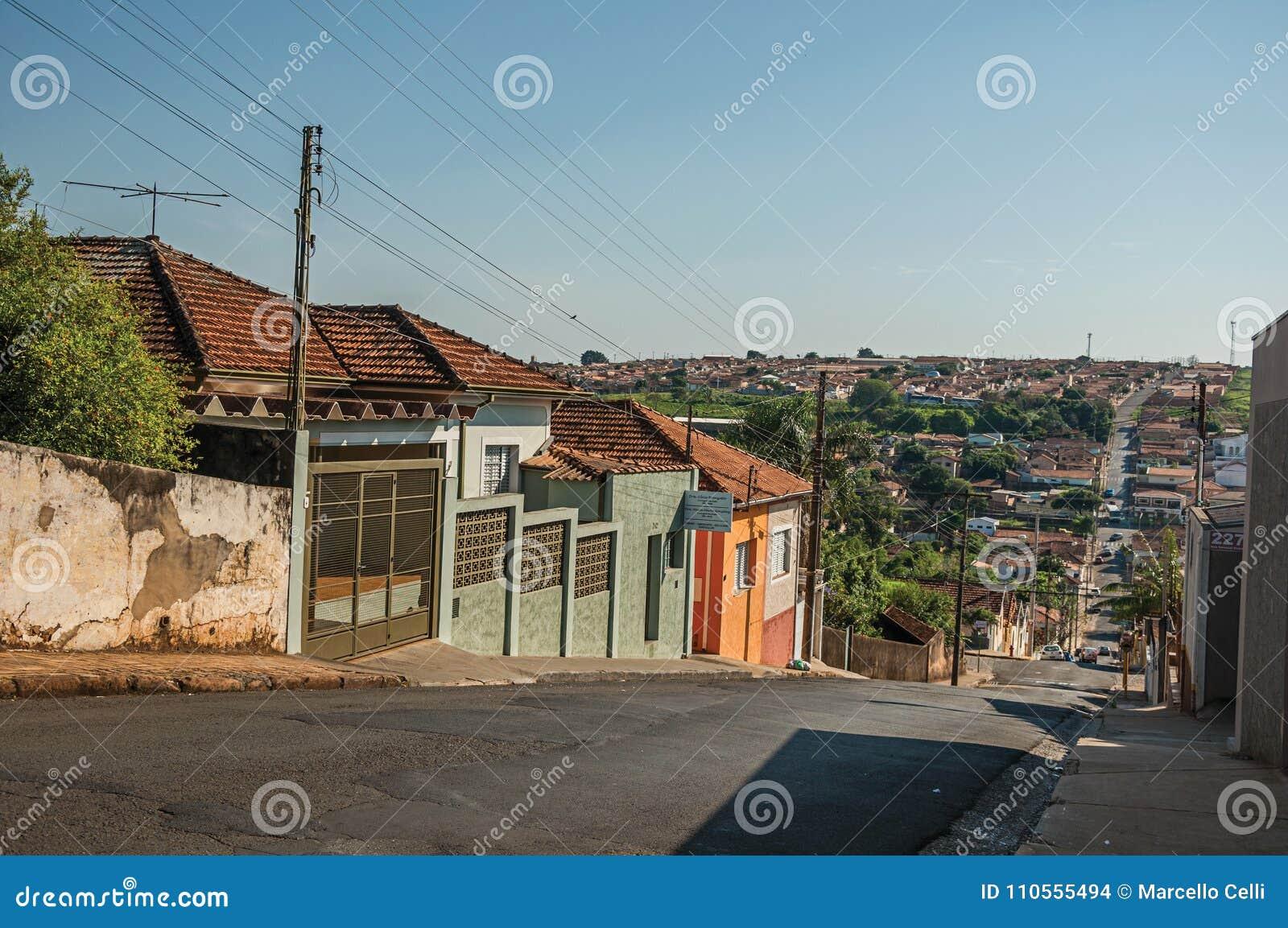 Opinião em declive da rua com paredes do passeio e as casas coloridas em um dia ensolarado em São Manuel